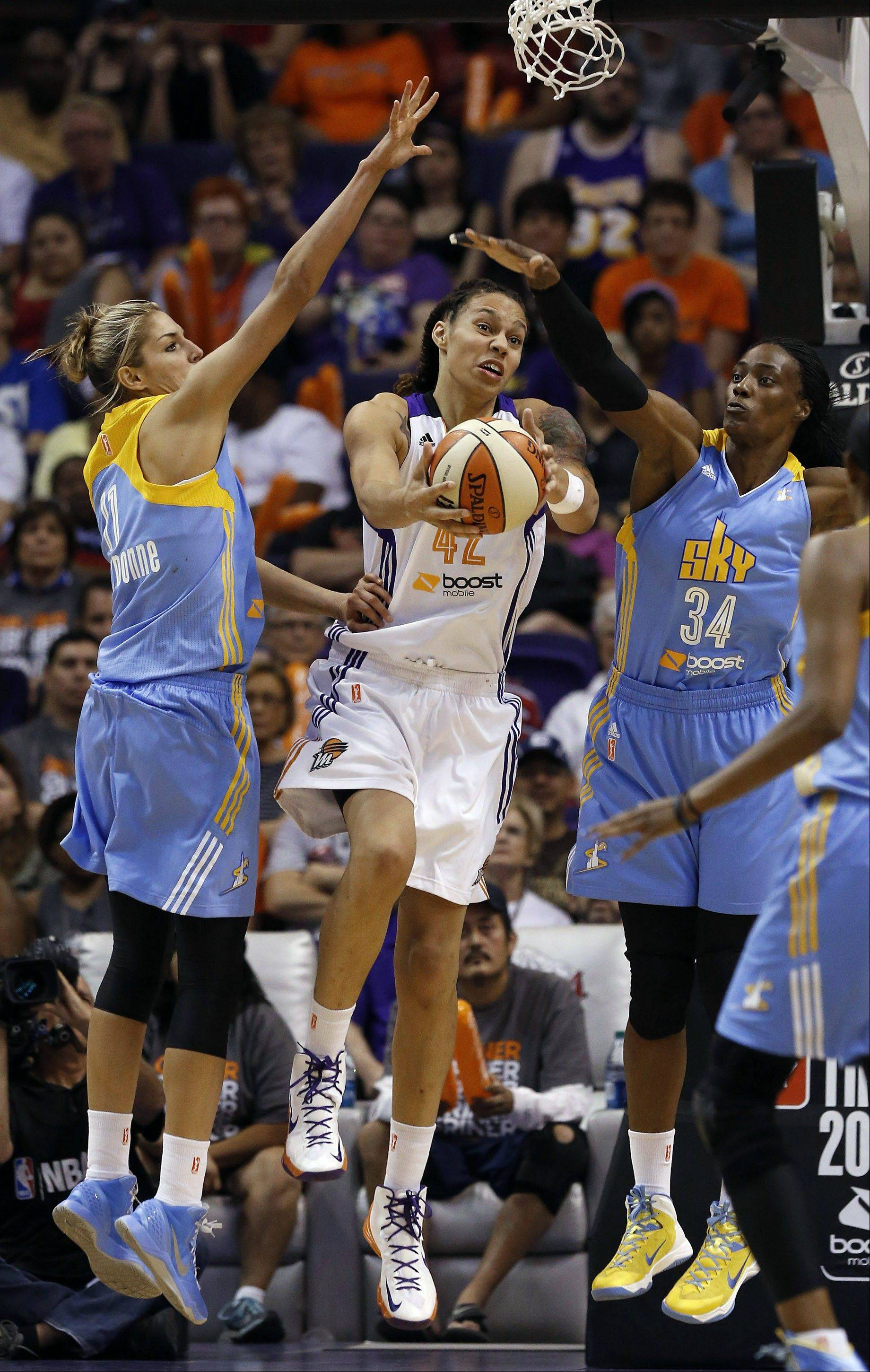 Elena Delle Donne, left, and Sky center Sylvia Fowles (34) defend Phoenix Mercury's Brittney Griner as she tries to go up for a shot in their WNBA opener on Monday.