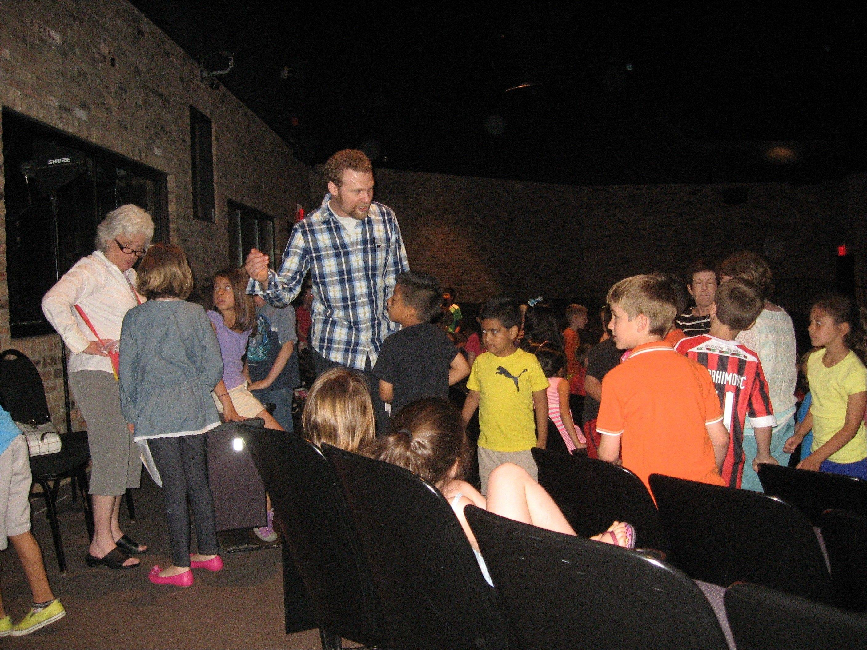 Jeremy Schaefer greets second-grade students following the performance.