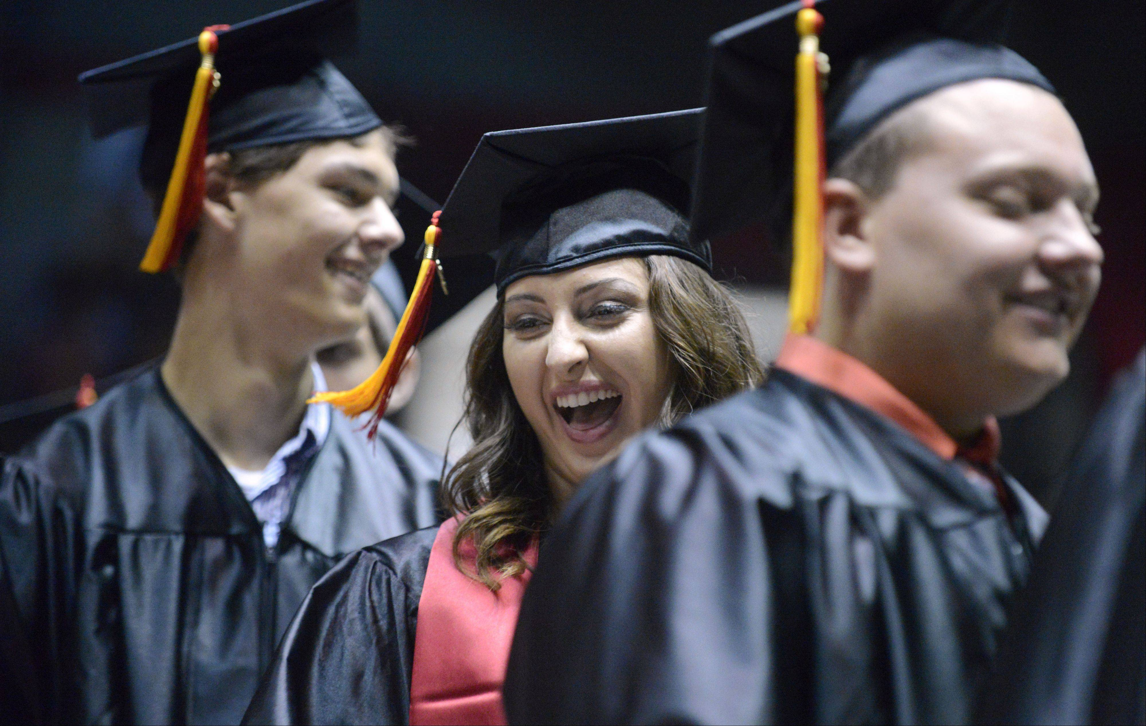 Anna Chorneyko laughs with classmates as her row prepares to go onstage to receive their diplomas at Batavia High School's commencement ceremony at the NIU Convocation Center on Friday, May 31.