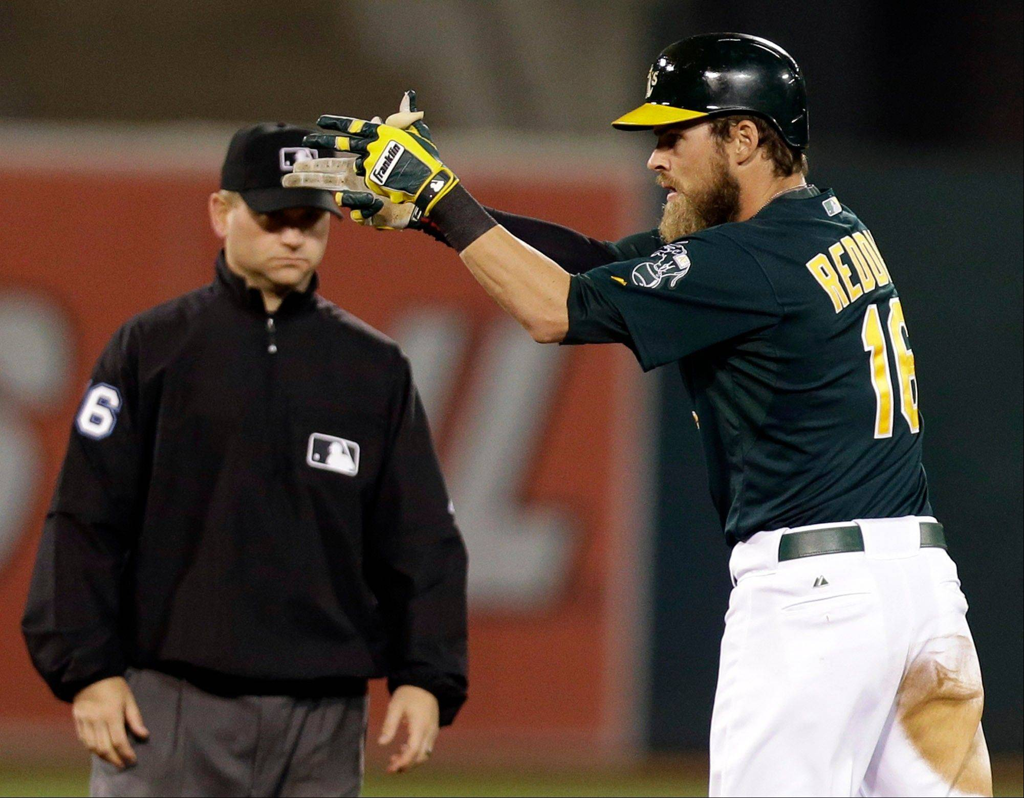 Oakland Athletics' Josh Reddick points to his dugout after driving in the first run of the game with an eighth-inning double against the Chicago White Sox on Friday in Oakland. The A's won the game, 3-0.