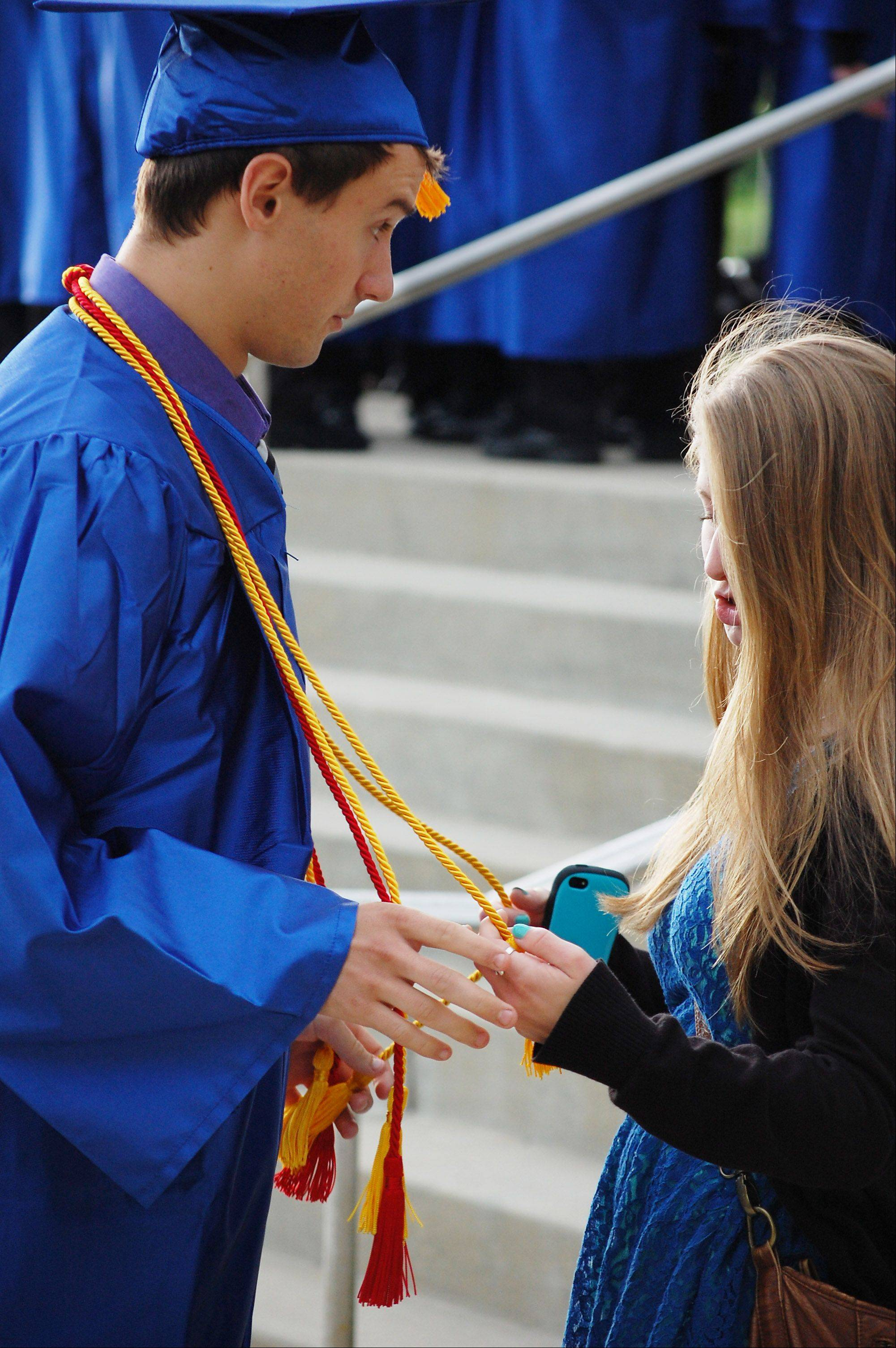 Graduate John Smith and Emma Rabelhofer, 19, of St. Charles prepare for the Burlington Central High School graduation ceremony Friday at Elgin Community College in Elgin.
