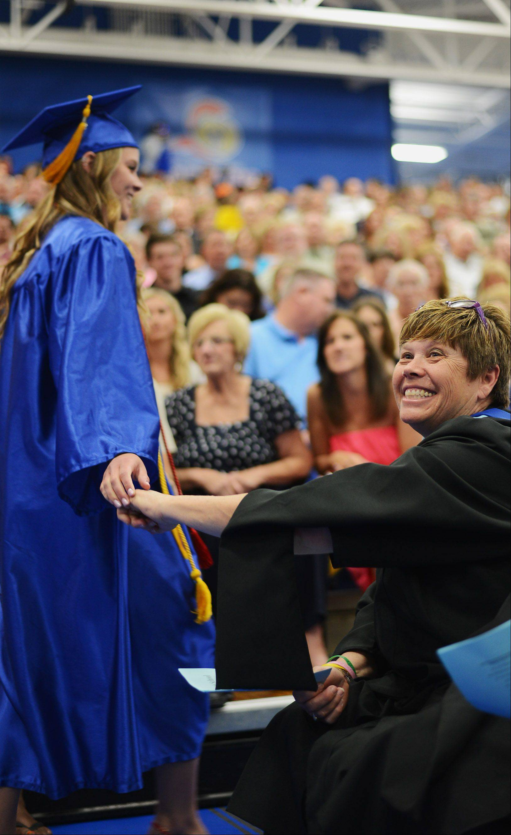 Deb Twenhafel congratulates her students after they collect their degrees at the Burlington Central High School graduation ceremony Friday at Elgin Community College in Elgin.