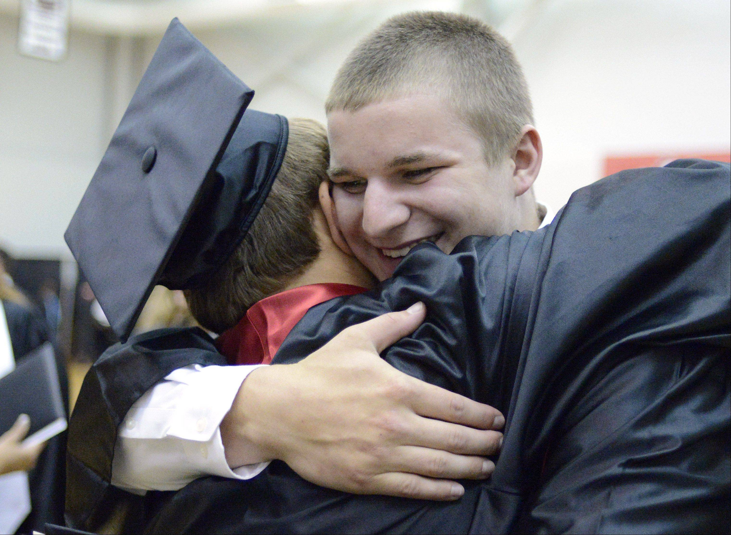 Benjamin Link, facing, embraces friend Dan Albrecht after they received their diplomas at Batavia High School's commencement ceremony at the NIU Convocation Center on Friday, May 31.