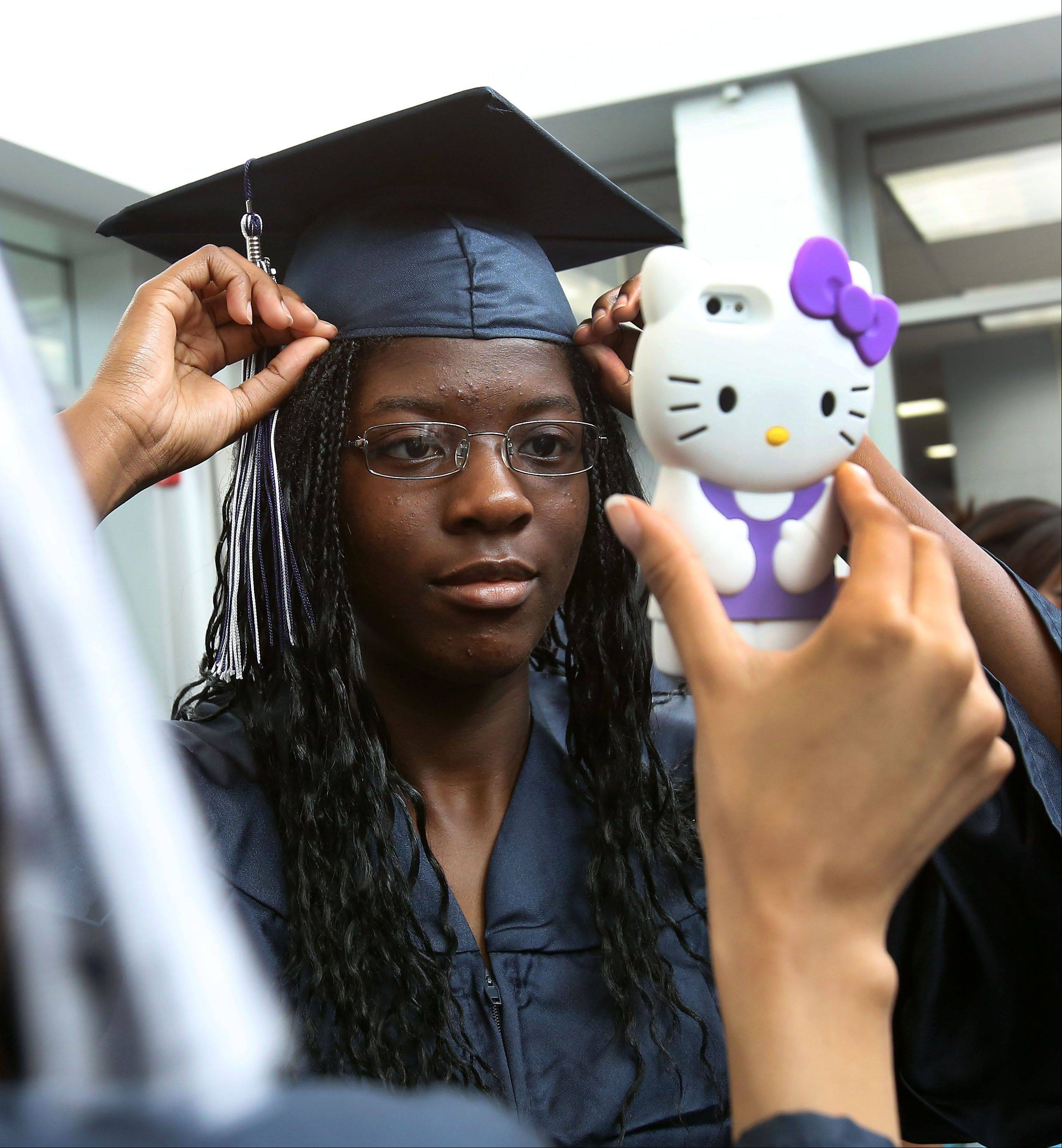 Adjowa Bio adjusts her cap using an iPhone camera before graduation at Lisle High School on Friday.