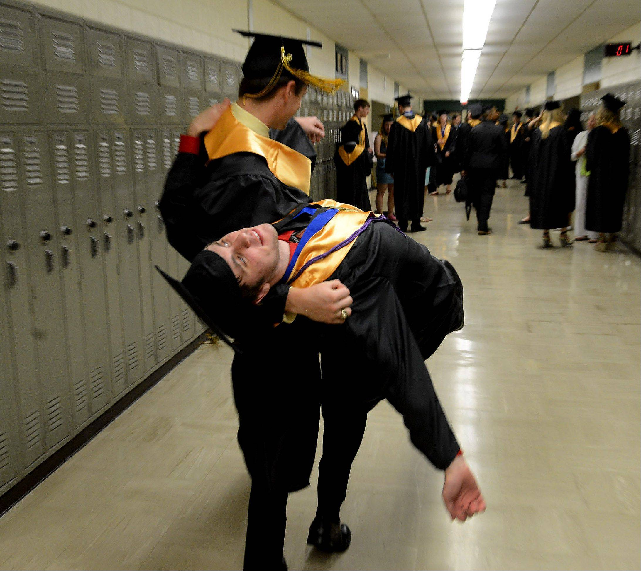 David Lawler, left, and Tom Sheridan feign a fainting spell while waiting for the Glenbard North High School graduation to begin.