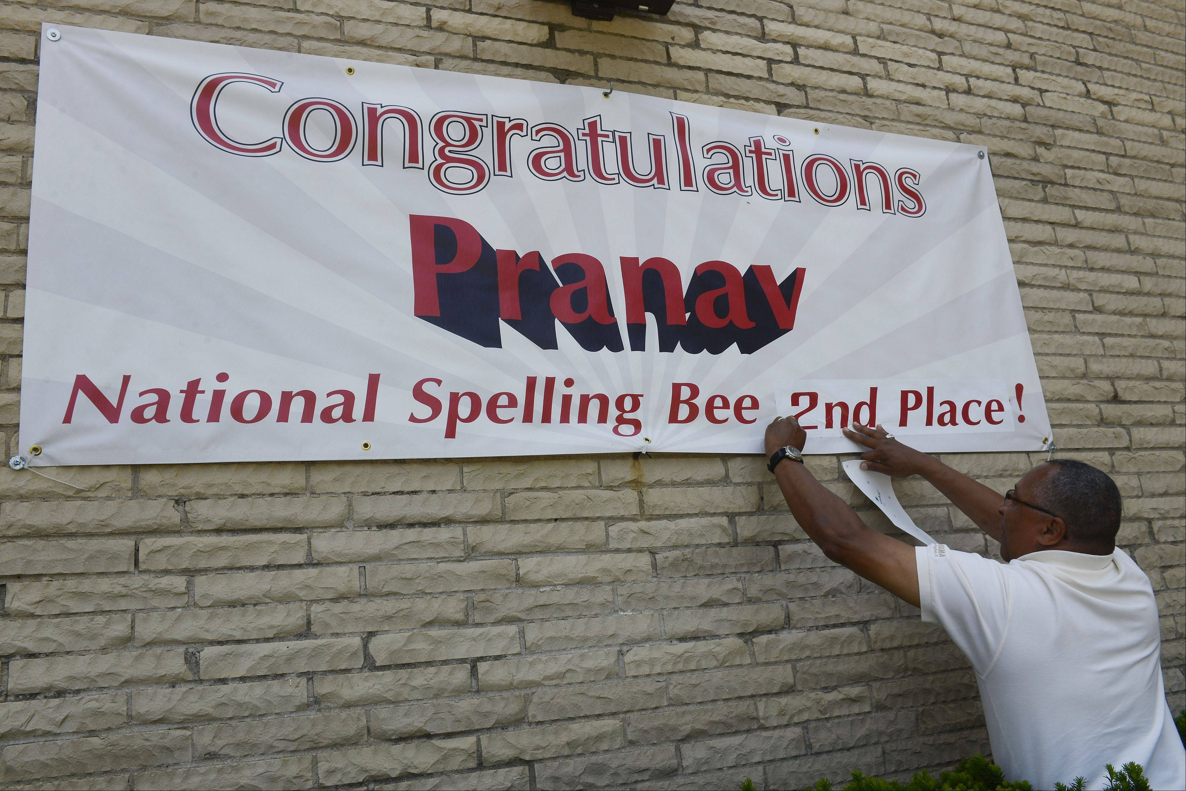 Vern Jones of Signarama updates a banner outside Barrington Middle School's Station Campus recognizing the finish by student Pranav Sivakumar in the Scripps National Spelling Bee.