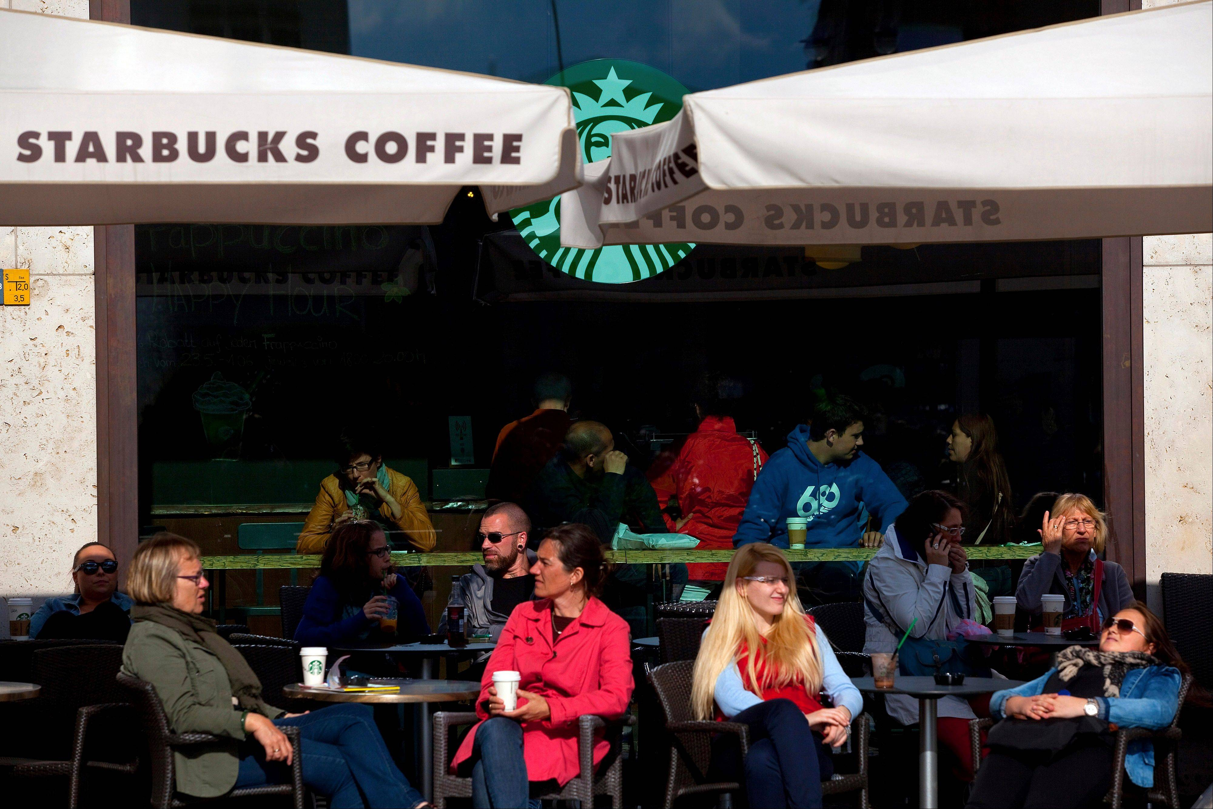 Customers sit Tuesday with beverages at tables outside a Starbucks Corp. coffee shop in Berlin, Germany.