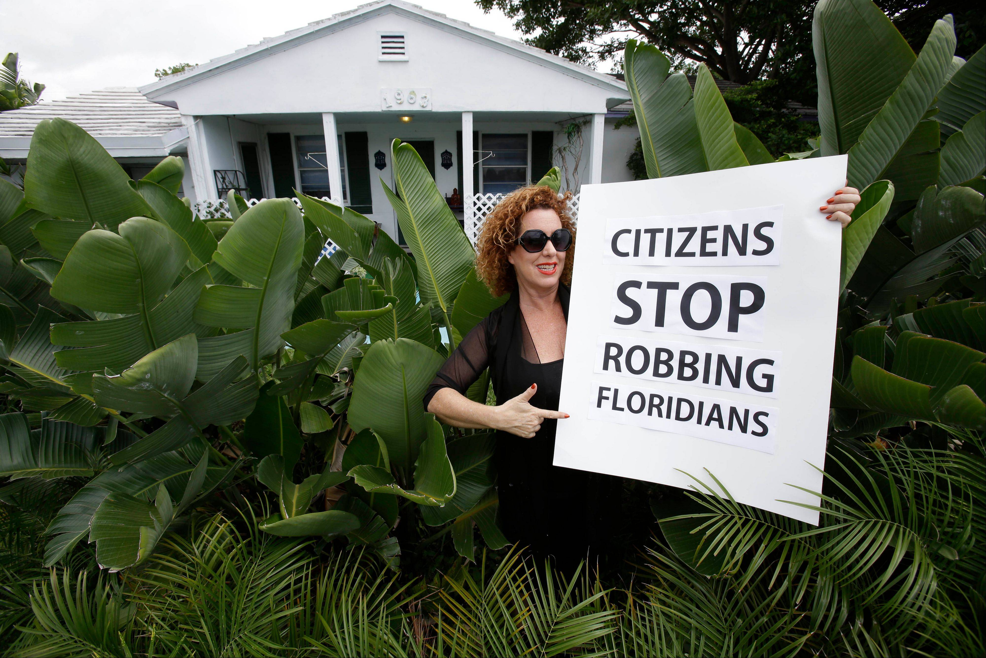 Nancy Loft Powers poses Monday with a sign she made in front of her home in Deerfield Beach, Fla. Powers had to sell other properties she owned because she could no longer afford the insurance.