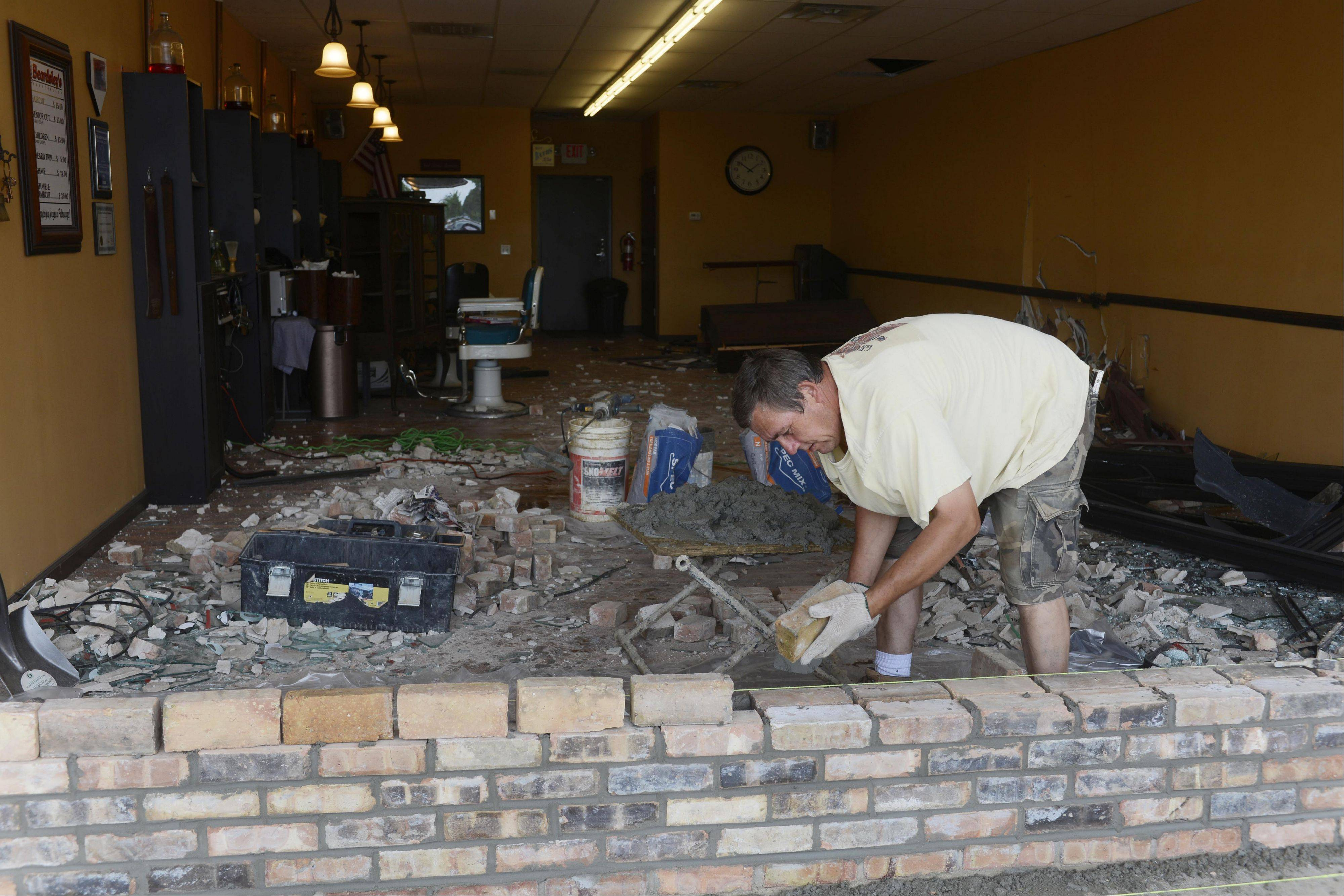 A masonry worker who declined to be identified replaces bricks at the front of Beardsley's Barber Shop in Elk Grove Village Friday afternoon after a car plowed through the window and entered the shop during the morning.
