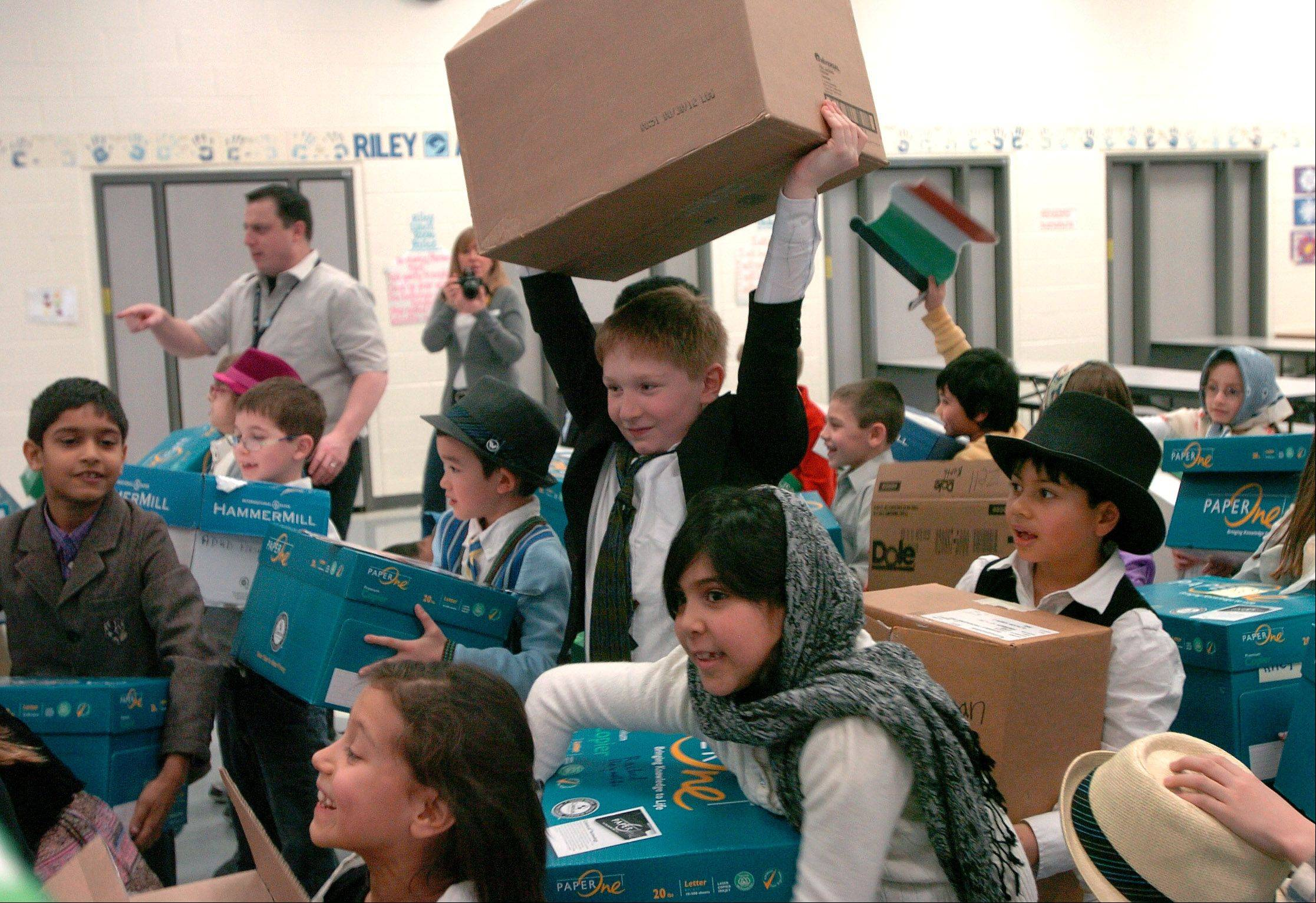 Riley School student Jack Cadre hoists his luggage in the ship's steerage while coming to America, as second-graders recreate the Ellis Island experience earlier in the school year.