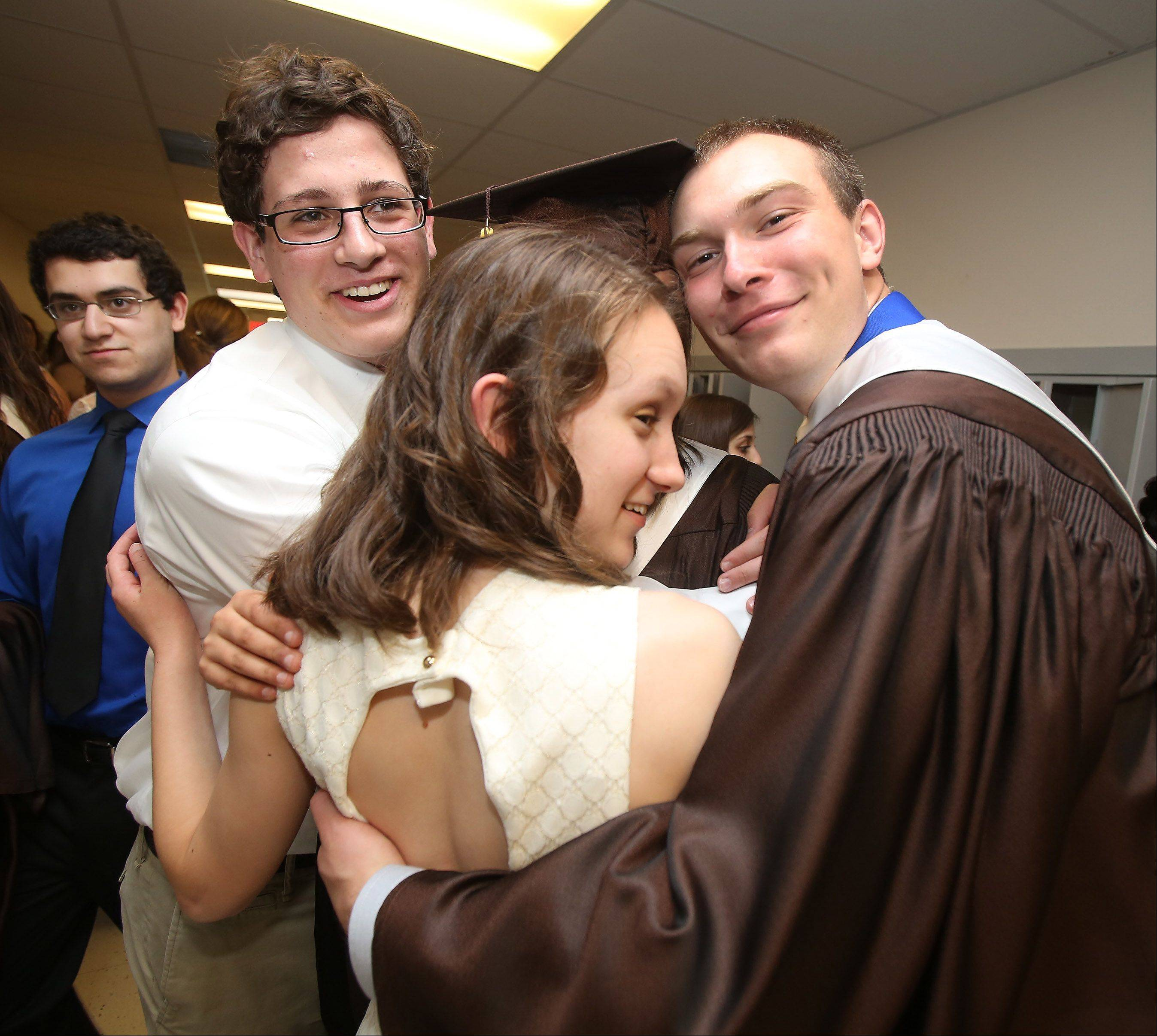 Dominic Fusco, left, Natalie Geoffroy, and Raymond Godlewski have a group hug before the commencement.