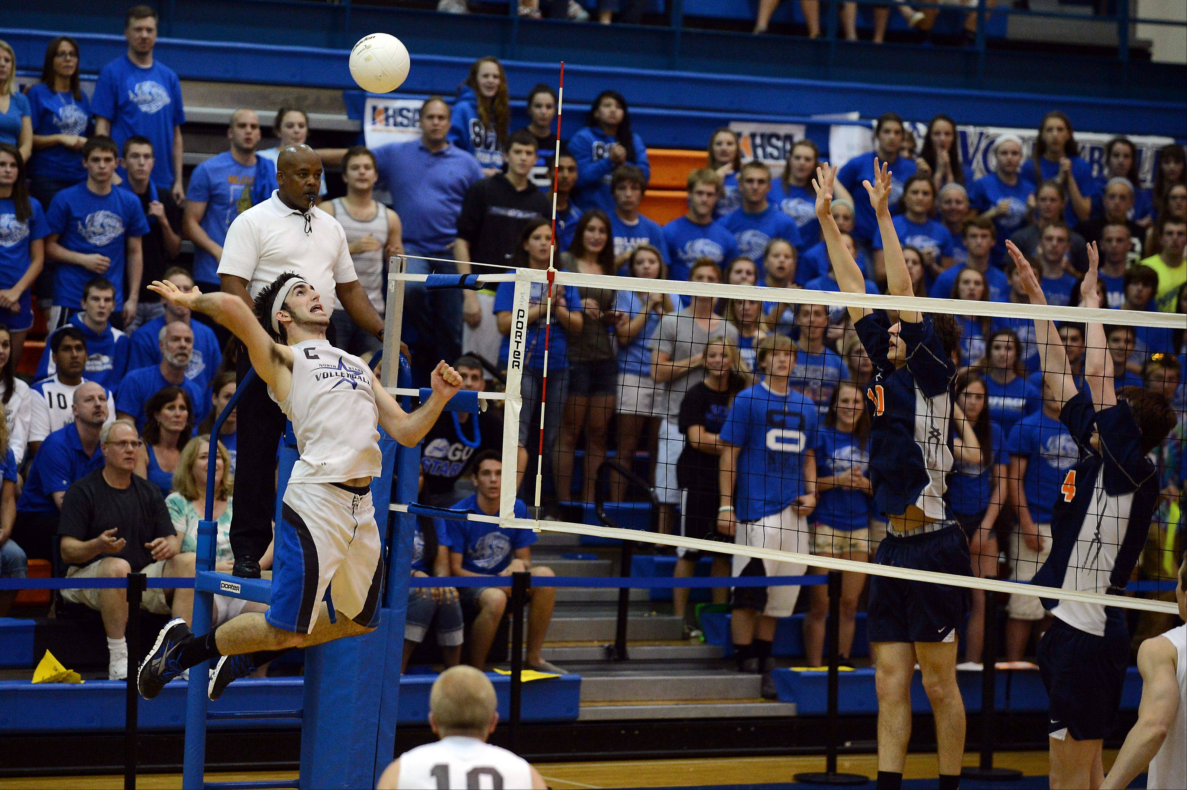 St. Charles North's Johathan Orech spikes the ball past Oak Park-River Forest defense in the best of three games at the boys volleyball state finals 2013 at Hoffman Estates High School on Friday.