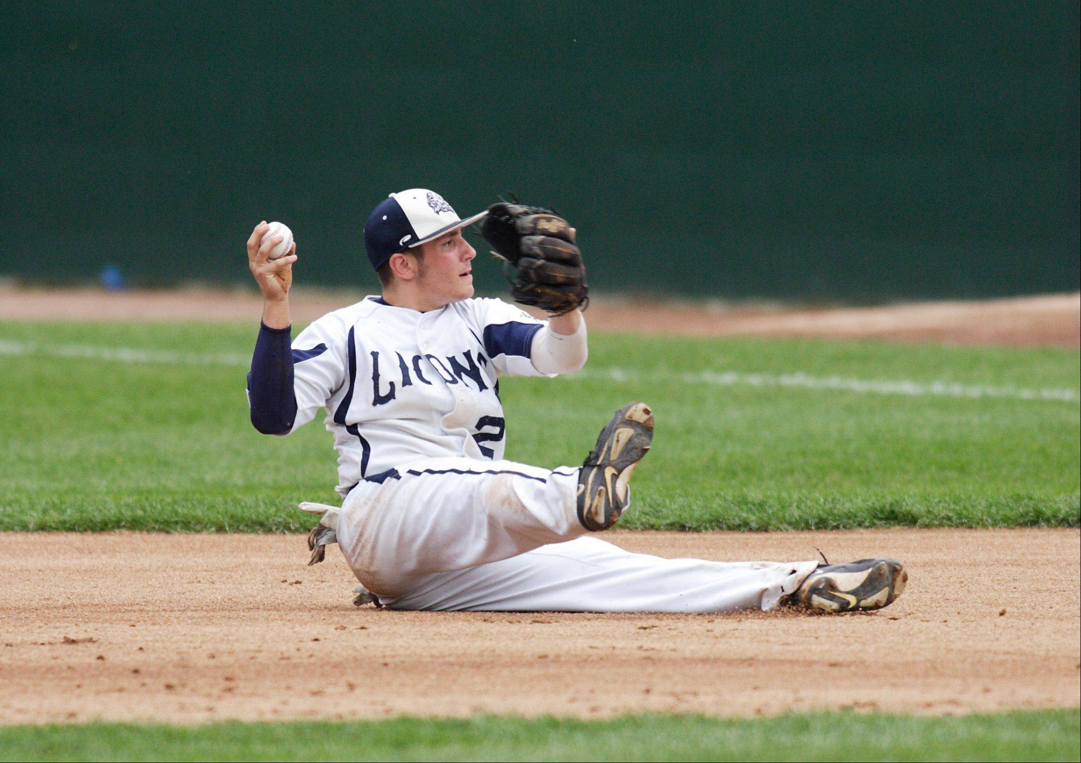 After making diving stop, Lisle's Cliff Krause makes a throw to first for an out in their IHSA state semifinal baseball game against Teutopolis. The Lions defeated the Wooden Shoes 2-1 to advance to Saturday's title game at Dozer Park in Peoria.