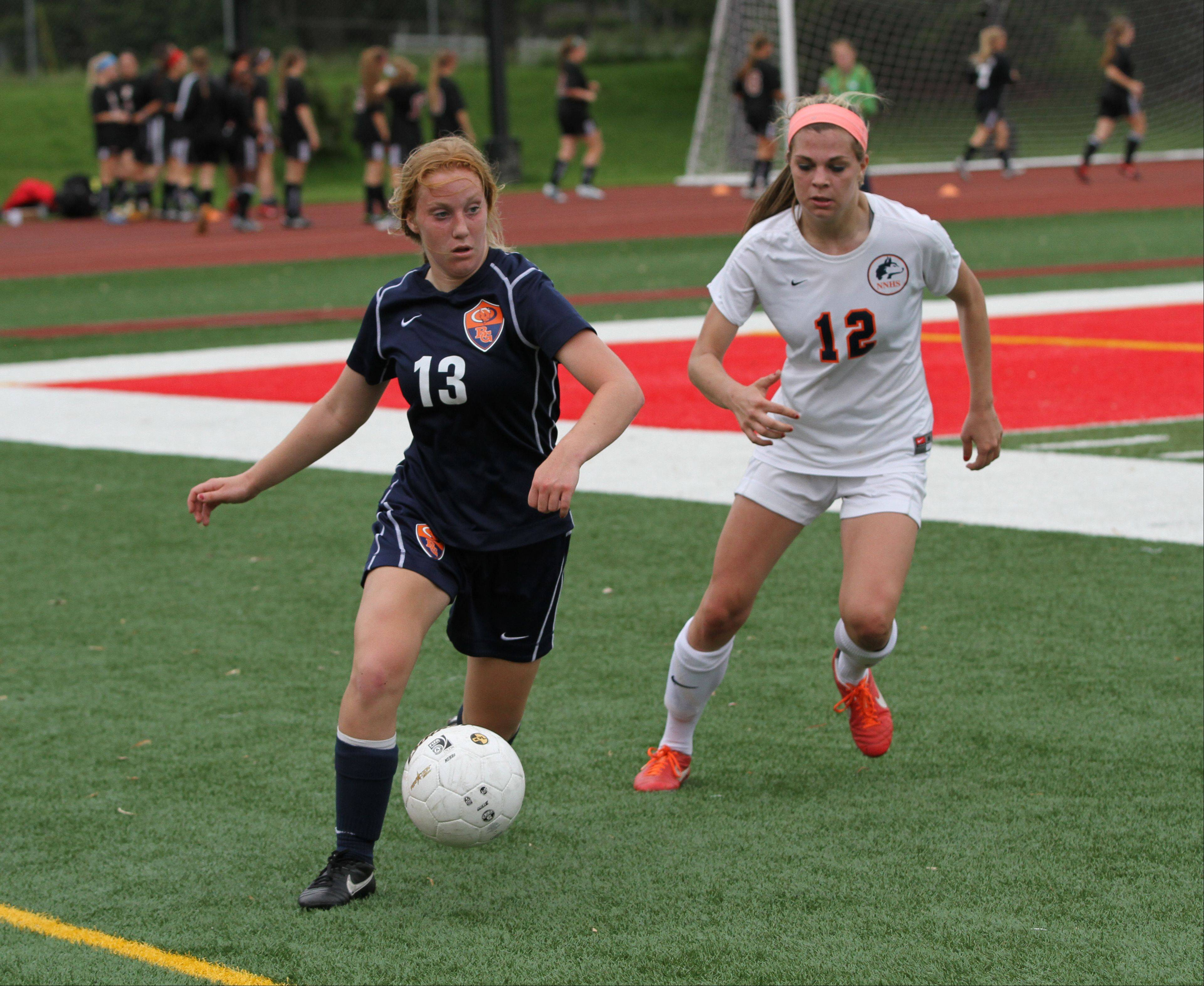 Buffalo Grove High School midfield Kelli Zickert plays the ball against Naperville North High School defenseman Abby Mangefrida at the girl soccer state semi-final game on Friday, May 31, 2013 at North Central College in Naperville, Ill.