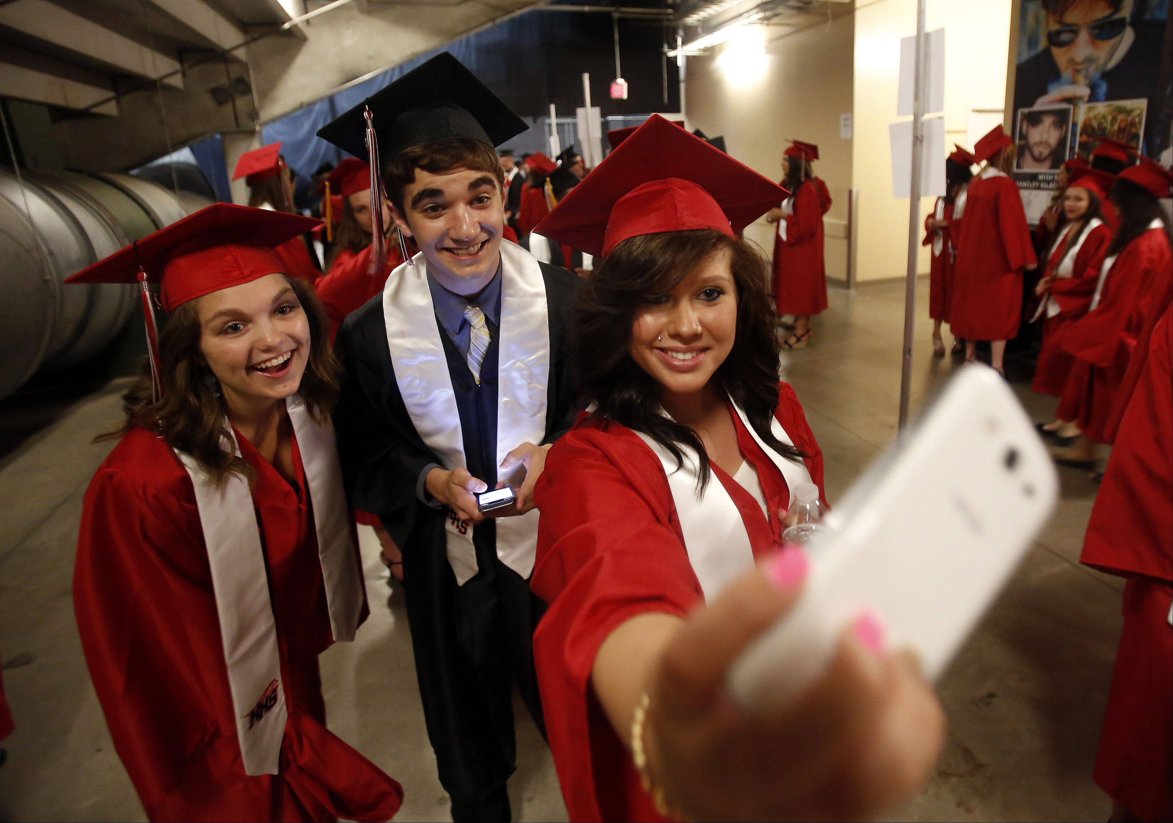 Sydney Skubal, from left, Joshua Smith and Nicole Smith pose for a quick cell phone picture before the Huntley High School 2013 Commencement ceremonies Saturday at the Sears Centre in Hoffman Estates.