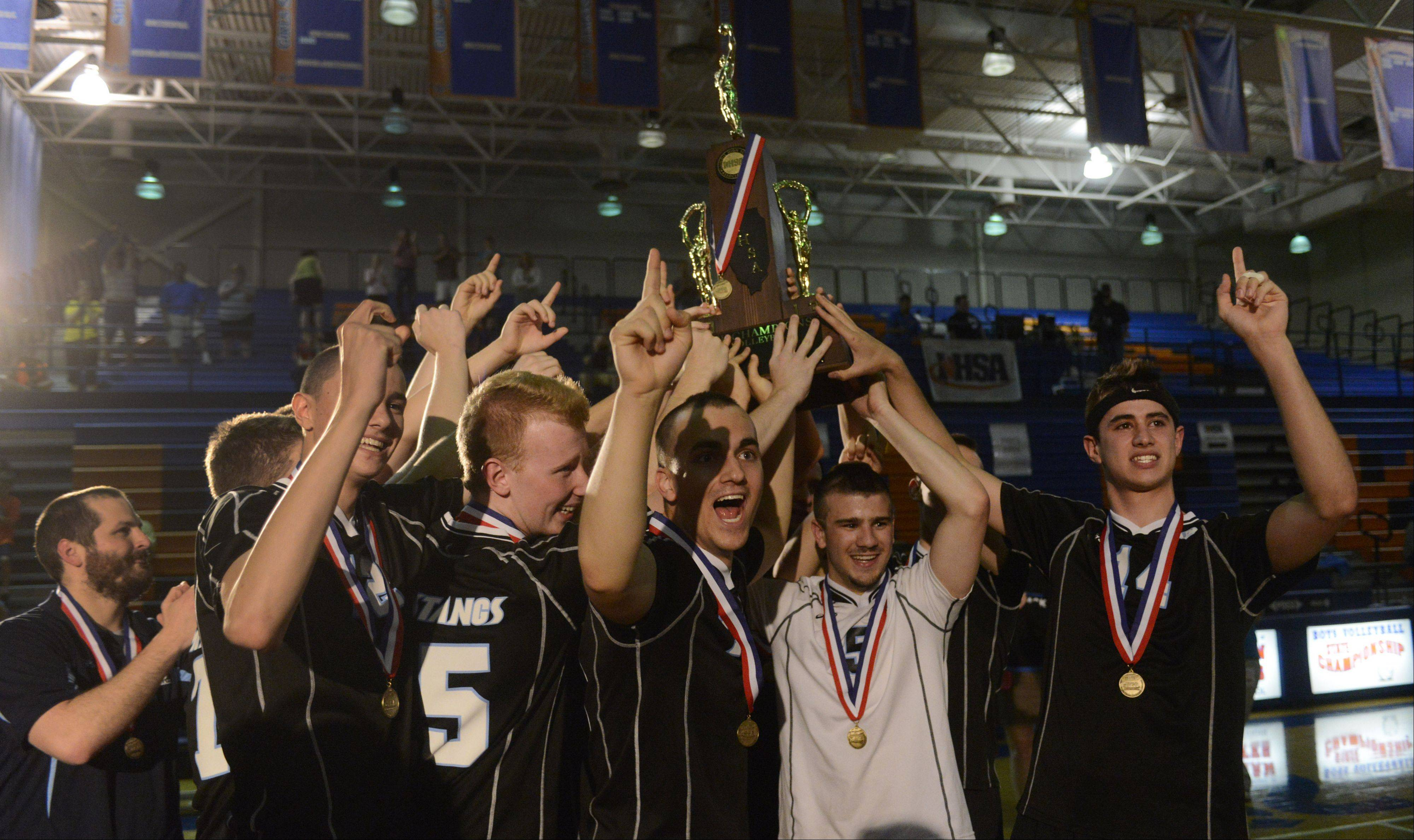 Members of the Downers Grove South boys volleyball team lift their first-place trophy following their win over Lincoln Way North in the state championship at Hoffman Estates High School Saturday.
