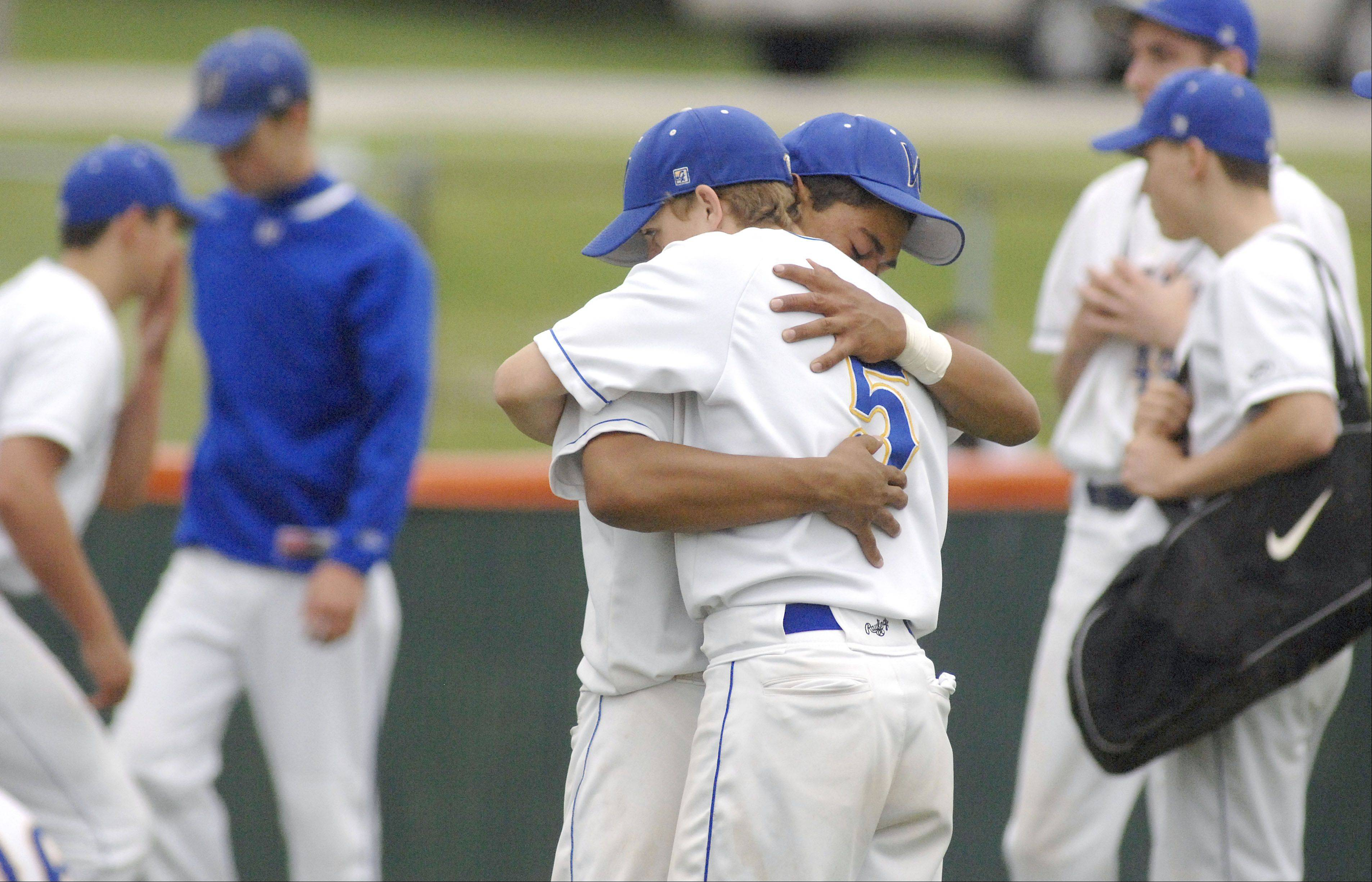 Wheaton North�s Jeff Harper, facing, gives a consoling hug to teammate and senior Cody Gregory after their Class 4A sectional championship loss to St. Charles East on Saturday, June 1.