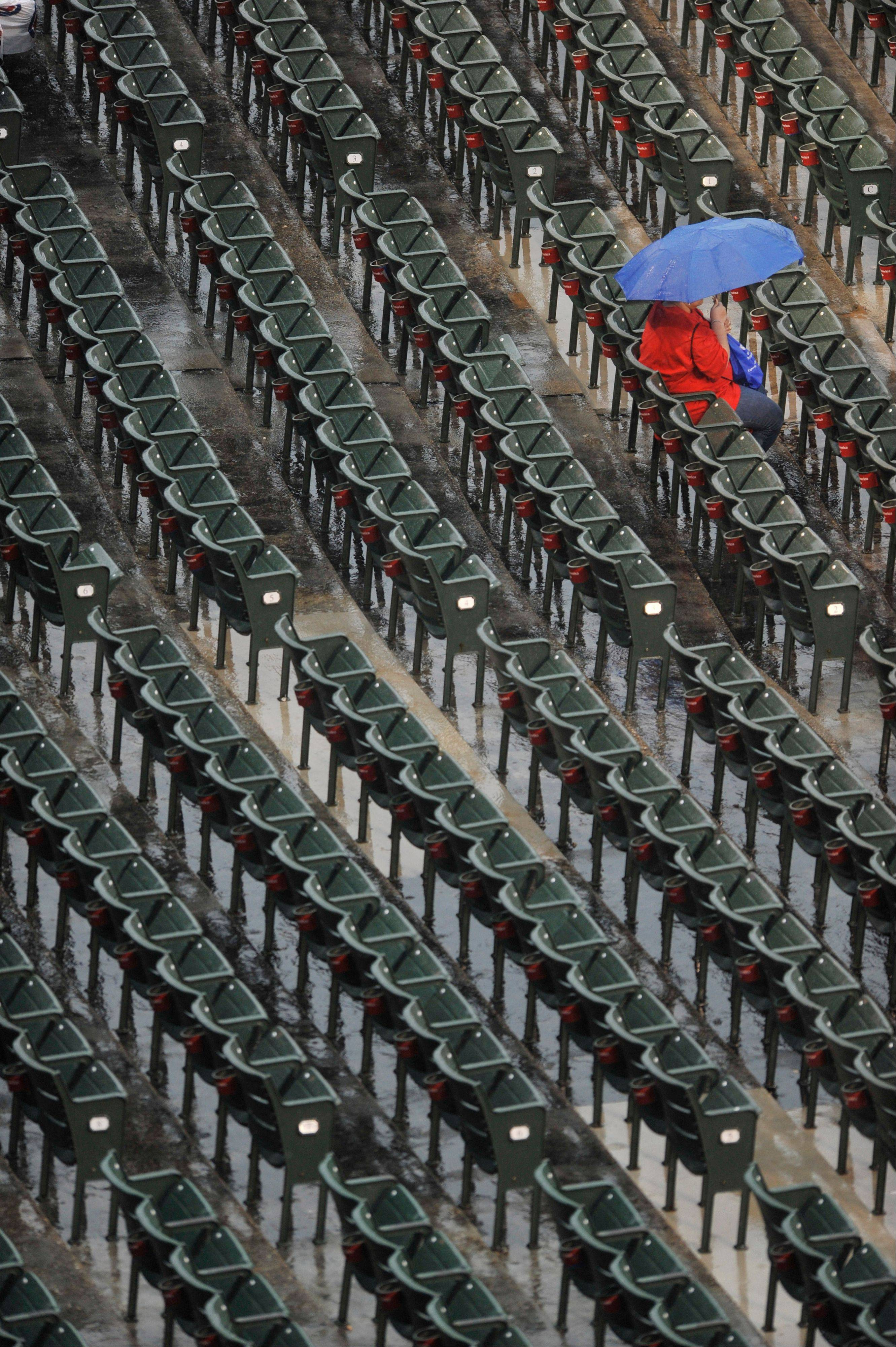 A fan looks on during a rain delay before a baseball game between the Chicago Cubs and the Arizona Diamondbacks at Wrigley Field in Chicago, Saturday, June 1, 2013.