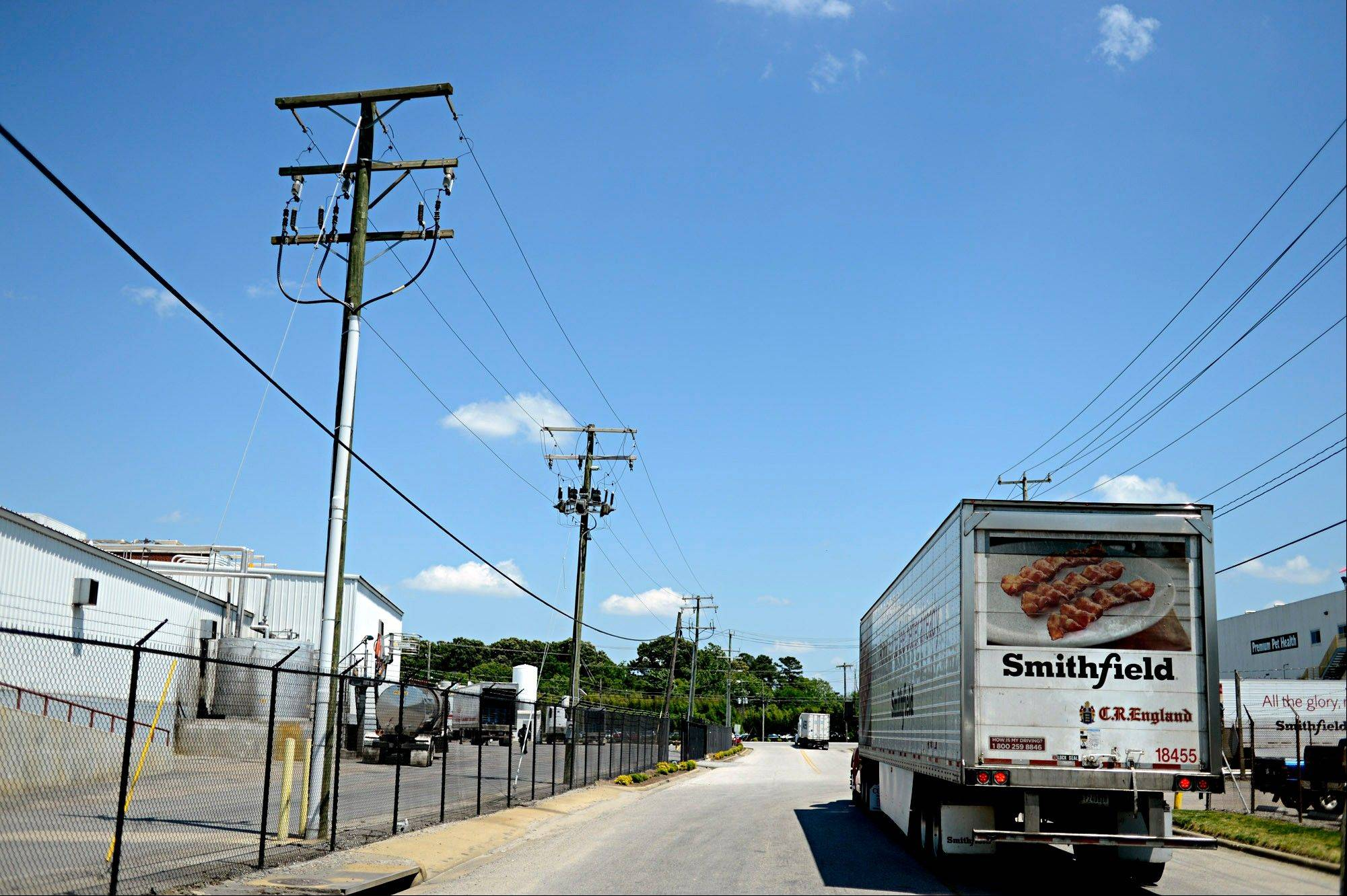 A truck waits outside the gates of Smithfield Foods Wednesday in Smithfield, Va. Smithfield Foods has agreed to be bought by Shuanghui International Holdings for about $4.72 billion.
