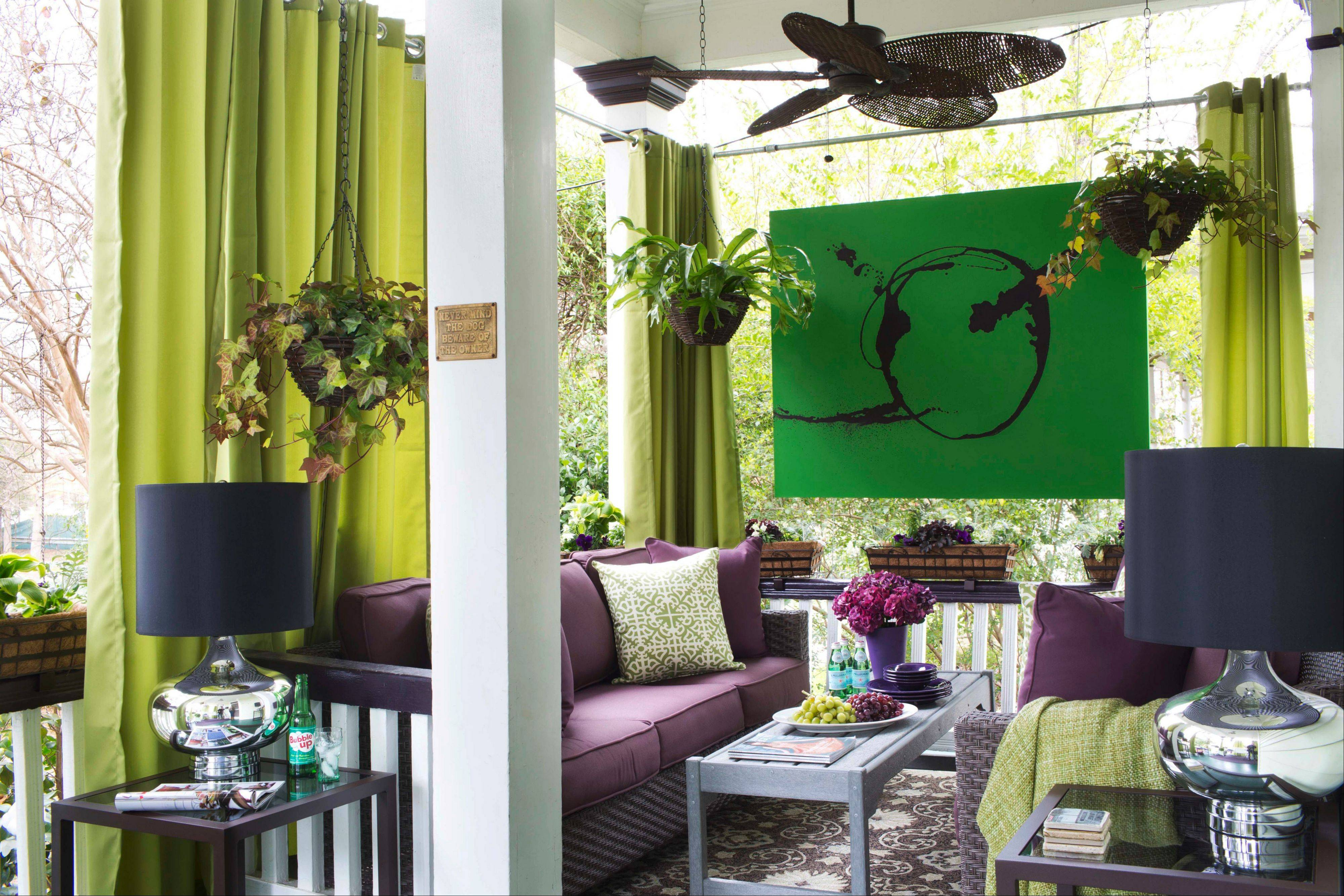 Drapery panels are added to this small porch to emphasize the house's tall ceiling. Flynn uses a few other tricks to make small outdoor spaces appear larger, such as hanging oversized art painted on a tent canvas.