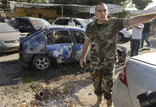 A Lebanese army officer stands next to a damaged car as he asks journalists to step back, at the scene where a rocket struck a car exhibit, at the Mar Mikhael district south of Beirut, Lebanon, Sunday May 26, 2013. Rockets slammed Sunday into two Beirut neighborhoods that are strongholds of Lebanon's Hezbollah group, wounding at least 4 people, Lebanese security officials and media said.