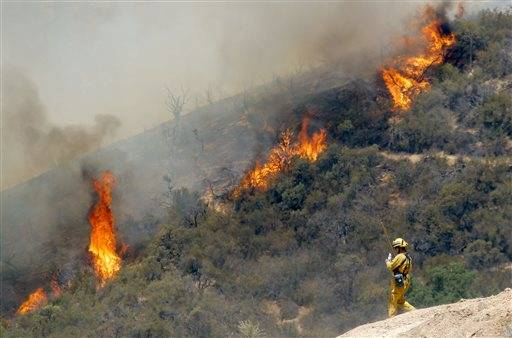 A firefighter watches a 1,400-acre wildfire northeast of Castaic, Calif., Friday May 31, 2013. Crews battling this wildfire in the mountains north of Los Angeles took advantage of cool morning weather Friday to make progress but scattered flames continued to climb hillsides. A flare-up prompted Los Angeles County sheriff's deputies to briefly evacuate about 25 homes along a canyon road in the Angeles National Forest Friday morning but residents were later allowed to return.