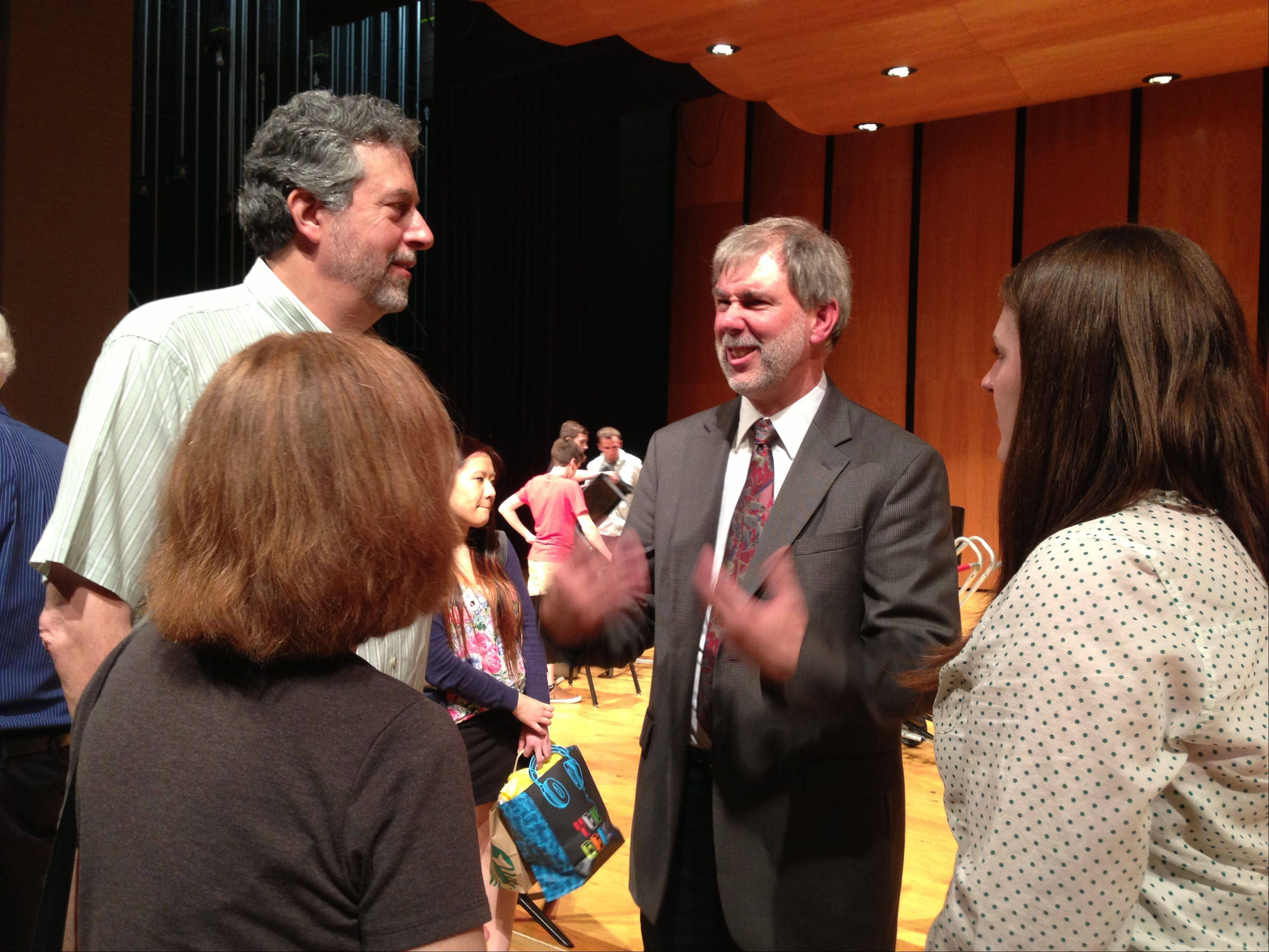 Retiring Vernon Hills High School fine arts supervisor and orchestra director Frank Lestina talks with Marc and Lori Abel and their daughter, Rebekah, a 2000 graduate of the high school, after a concert honoring Lestina Saturday afternoon.