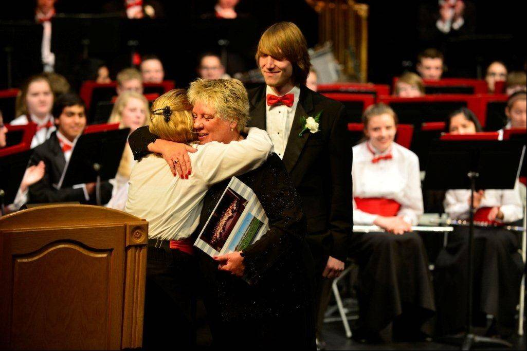 Raeleen Horn hugs her students during her final concert. She is retiring Friday after working for 33 years as a band director at Palatine High School.