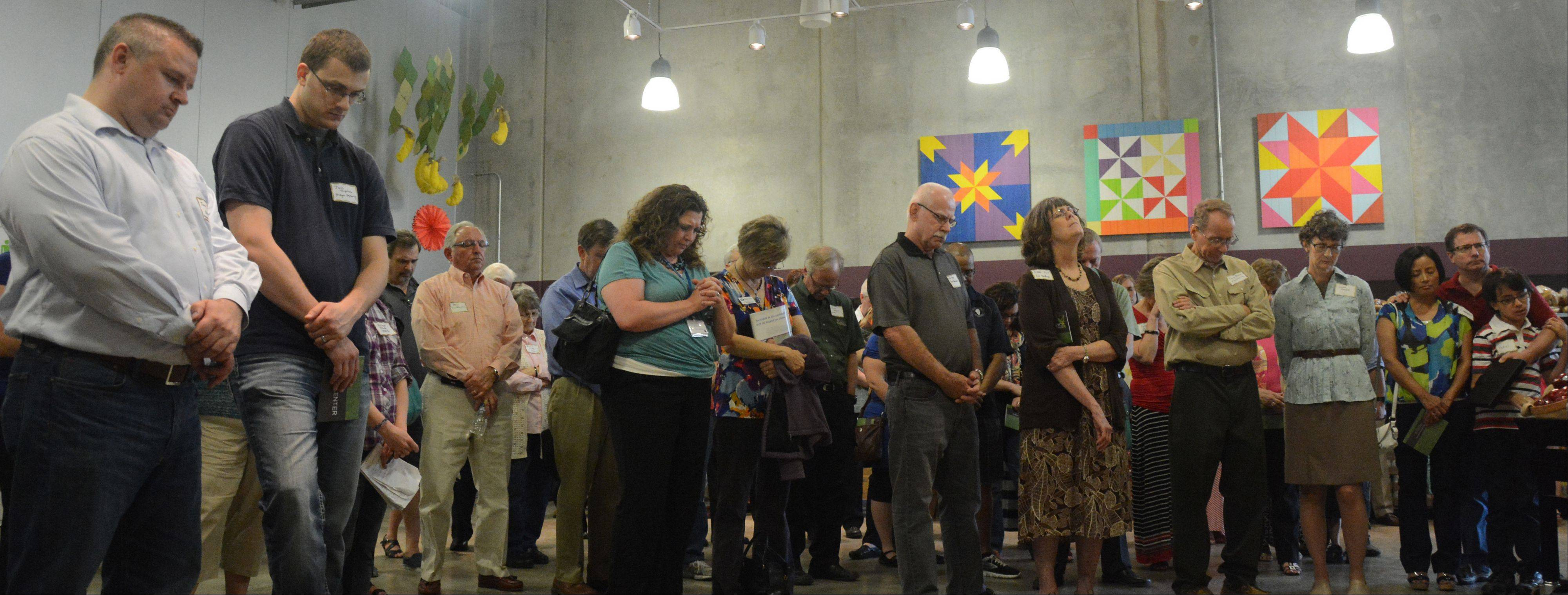 Attendees pray during the dedication of the Care Center at Willow Creek Community Church on Friday in South Barrington