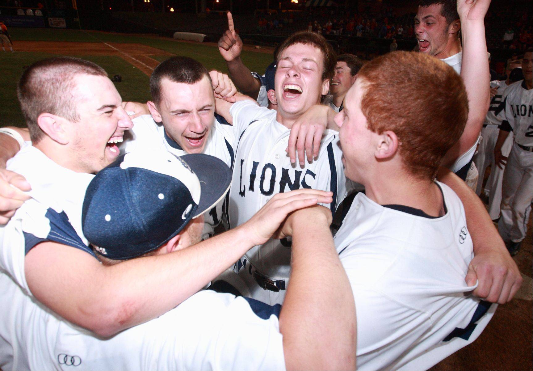 June 1, 2013 - Peoria, IL - Kevin Coppin lets out a loud yell with teammates as the Lions celebrate their state champion status at the IHSA state baseball tournament Saturday evening. Lisle defeated Pleasant Plains 10-1 to win the Class 2A title. [Photo: PhotoNews/Clark Brooks]