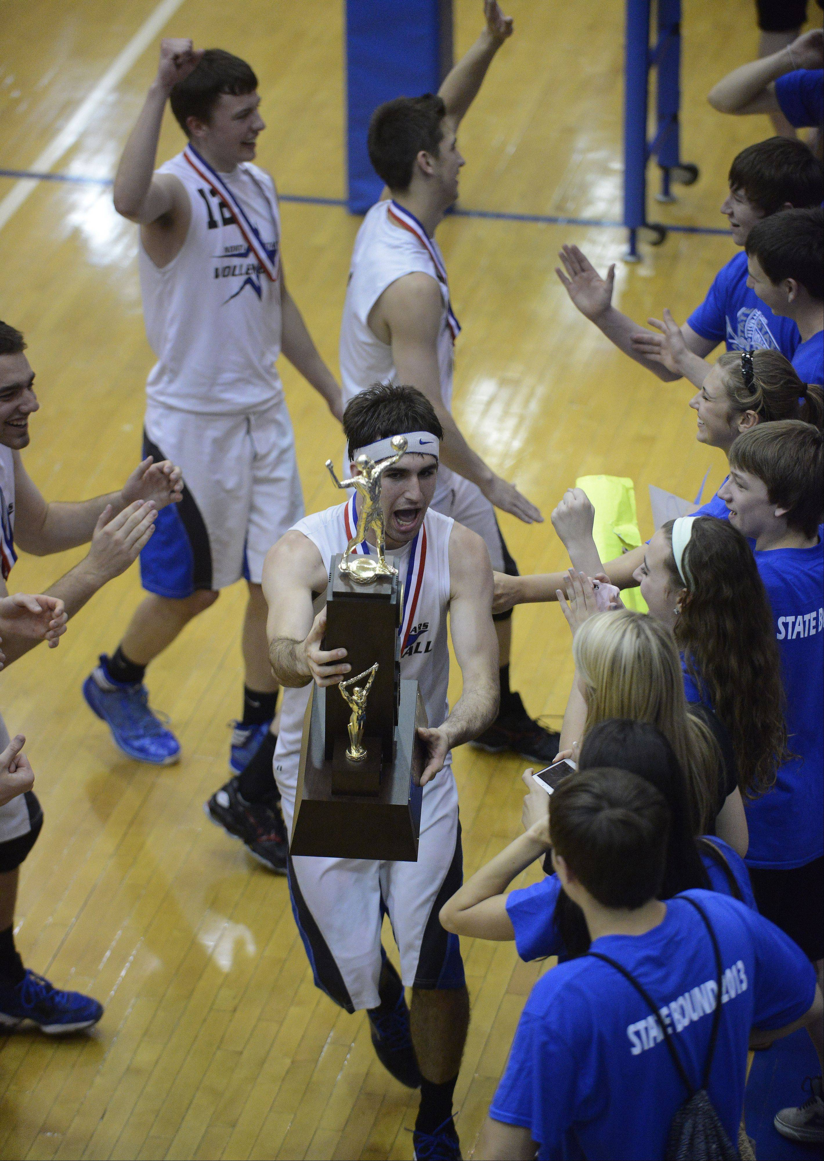 Jonathan Orech of St. Charles North shows the third-place trophy to fans following the team's victory over Glenbrook South at Hoffman Estates High School Saturday.
