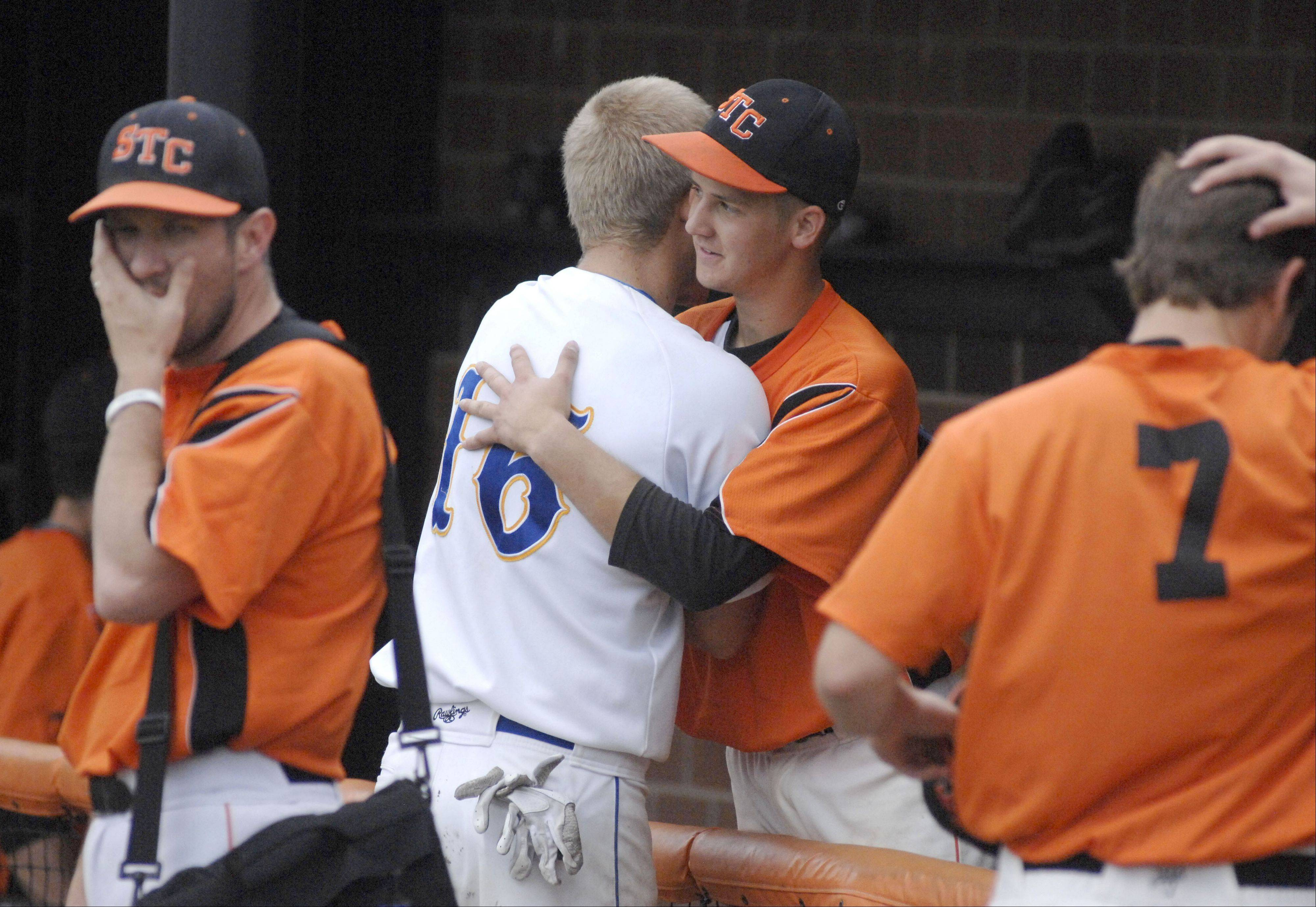 Wheaton North's Tom Cassier congratulates St. Charles East's Adam Rojas in the Saints dugout after St. Charles East's Class 4A sectional championship win on Saturday, June 1.