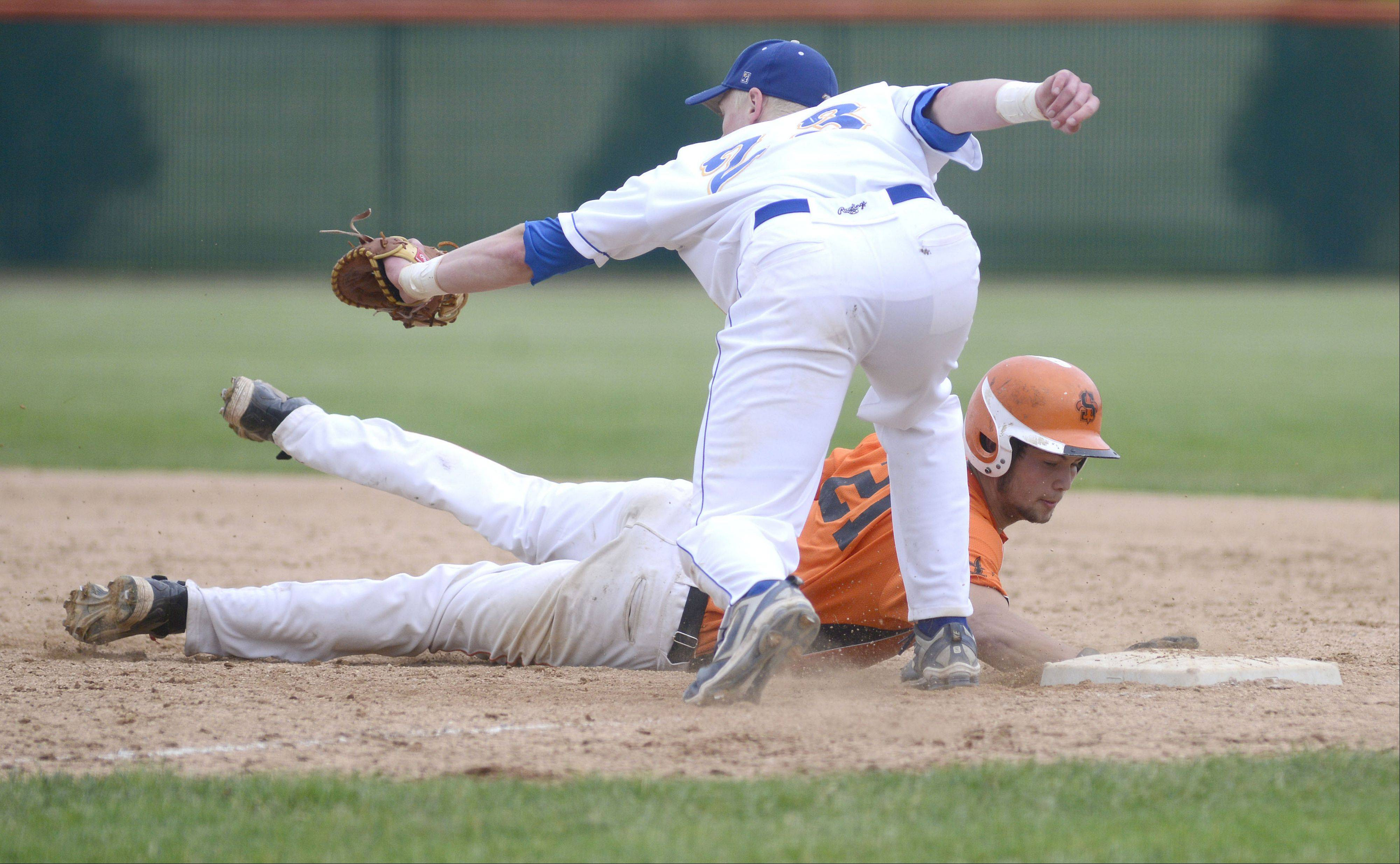 St. Charles East's Brannon Barry is safe from Wheaton North's John Peltz on first base in the third inning of the Class 4A sectional championship in St. Charles on Saturday, June 1.