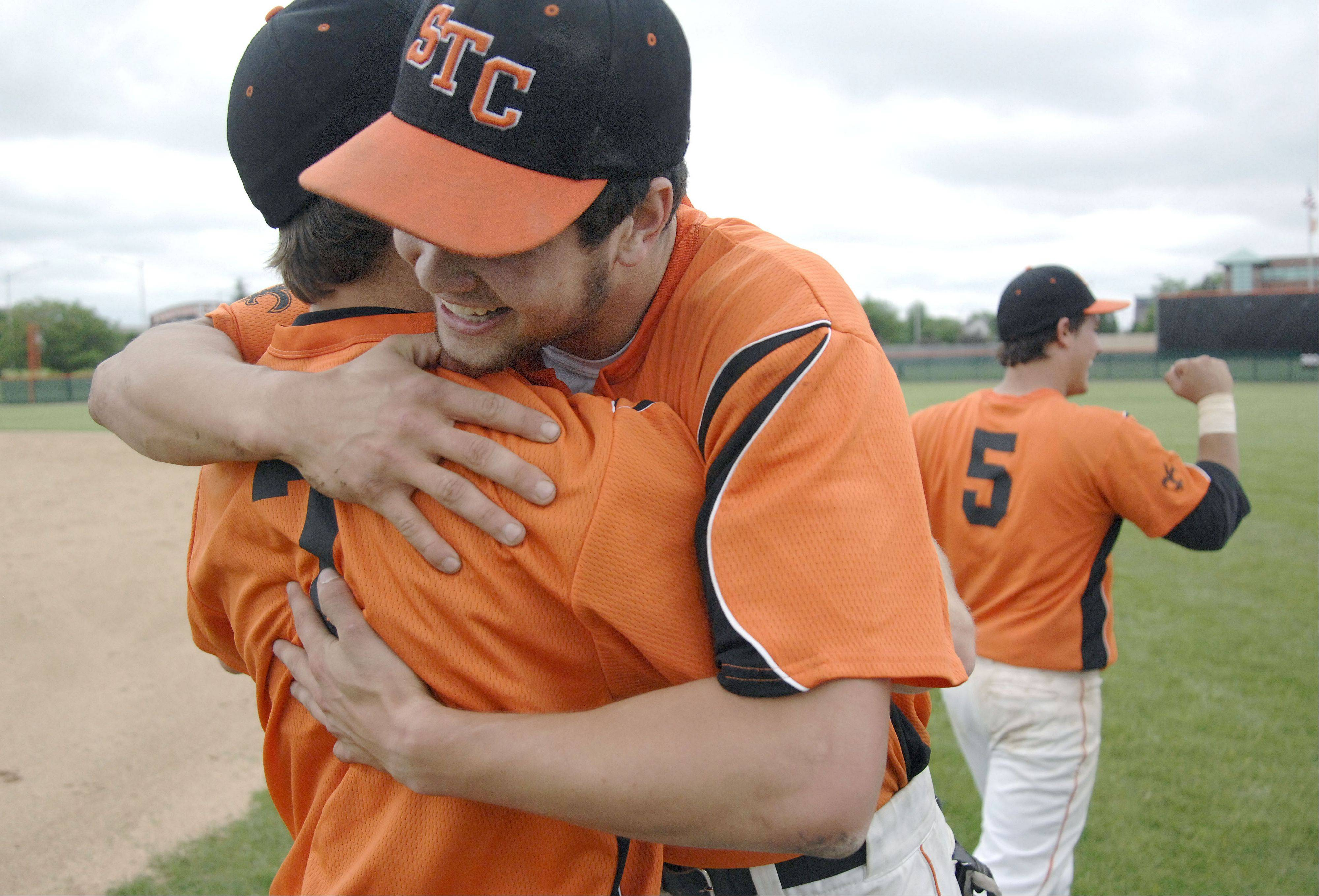 St. Charles East's Nick Huskisson (7) and Brannon Barry embrace while teammate Anthony Sciarrino pumps his fist after their Class 4A sectional championship over Wheaton North on Saturday, June 1.