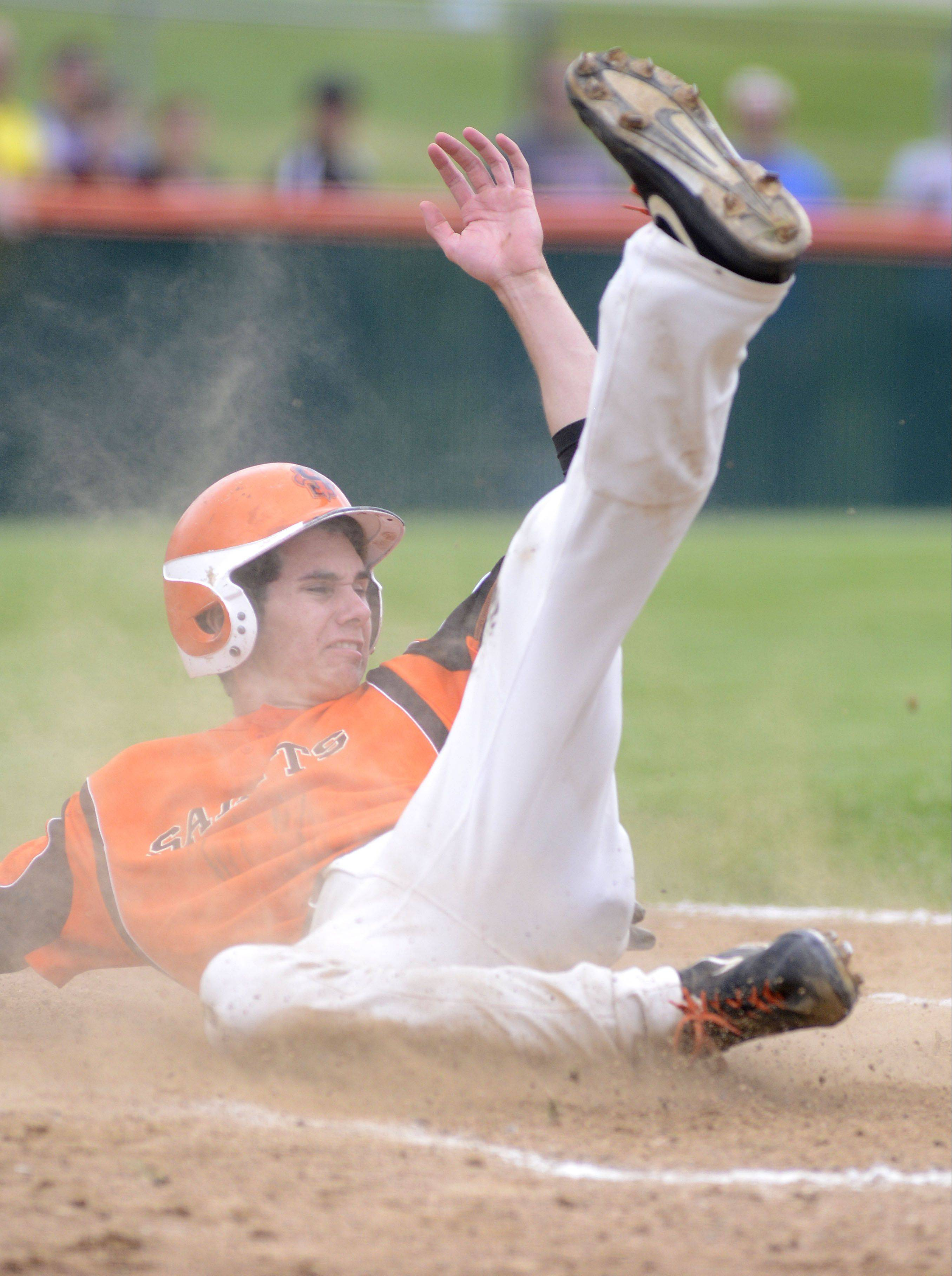 St. Charles East's Sean Dunne slides safely into home plate in the fifth inning.