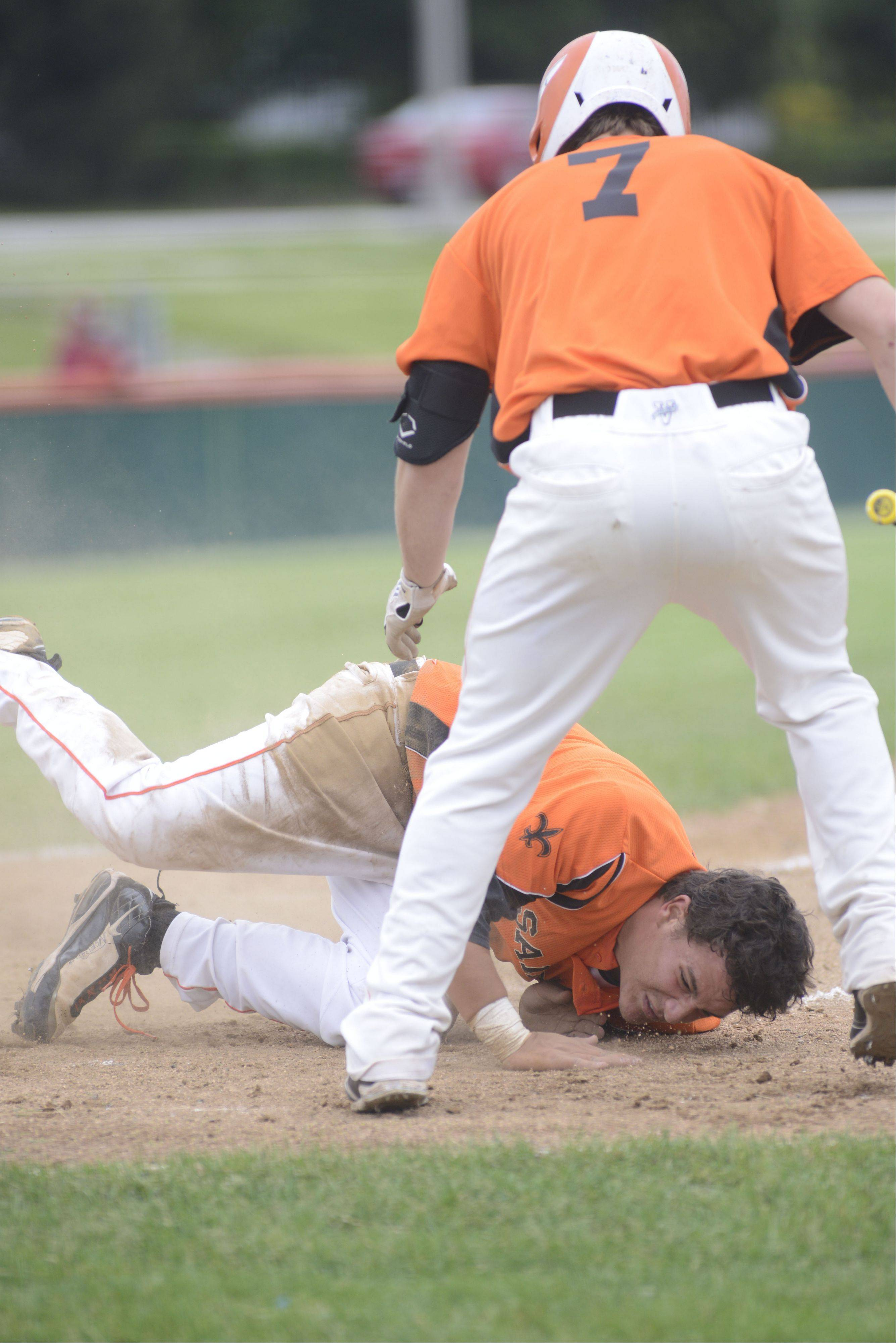 St. Charles East's Anthony Sciarrino tumbles in the dirt after a headfirst slide into home plate in front of teammate Nick Huskisson to break the tie in the fifth inning of the Class 4A sectional championship vs. Wheaton North on Saturday, June 1.