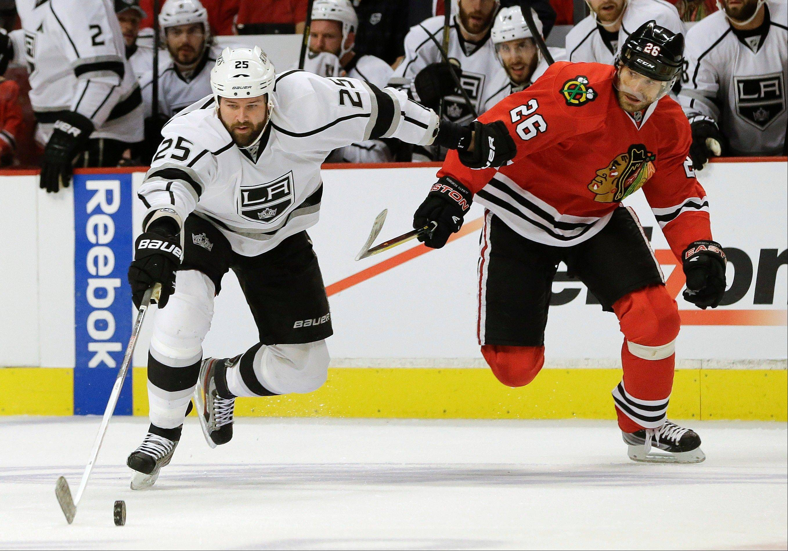 Los Angeles Kings left wing Dustin Penner (25) maintains control of the puck against Chicago Blackhawks center Michal Handzus (26) during the first period of Game 1 of the NHL hockey Stanley Cup Western Conference finals, Saturday, June 1, 2013, in Chicago.