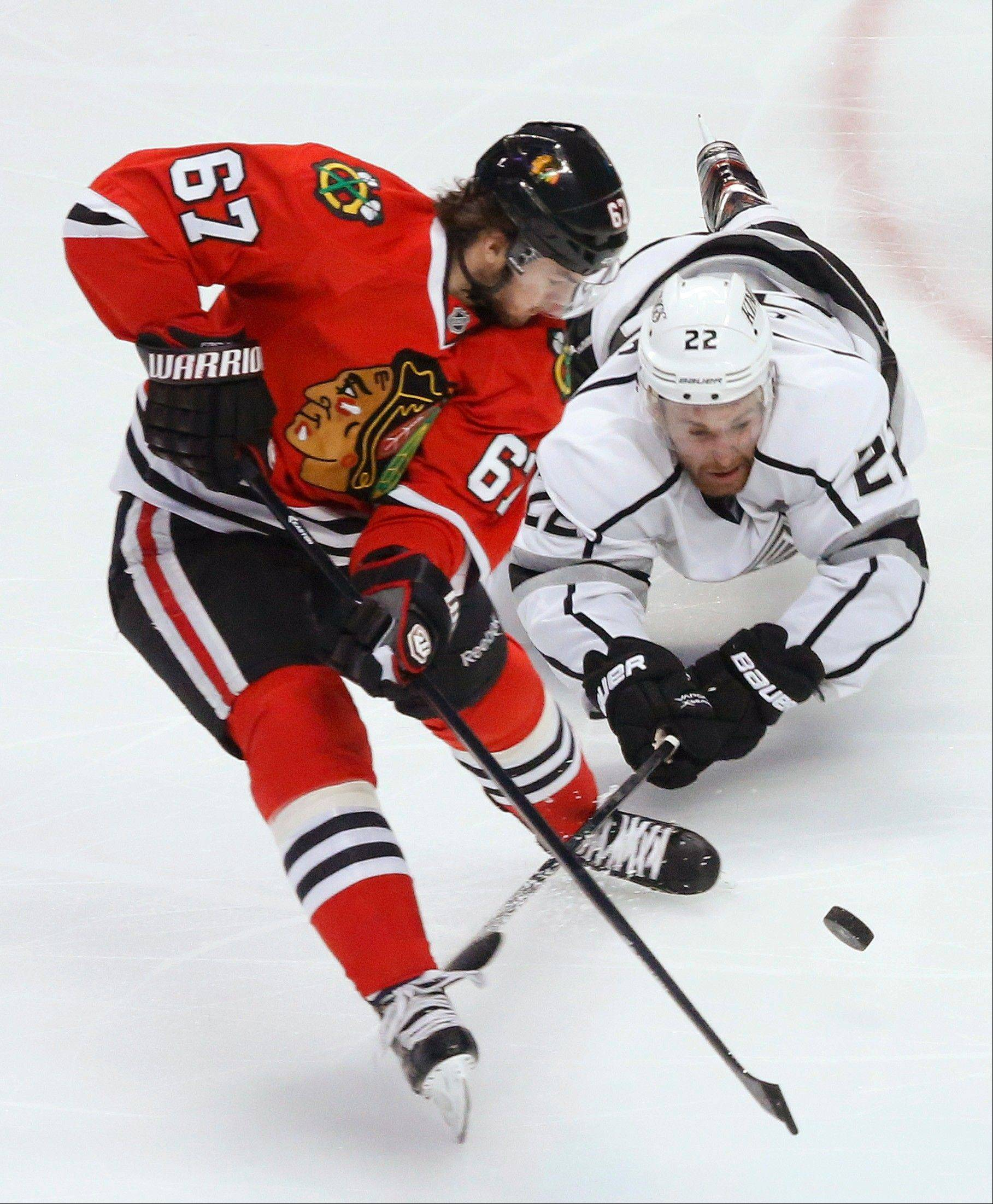 Los Angeles Kings center Trevor Lewis (22) dives for the puck against Chicago Blackhawks center Michael Frolik (67) during the second period of Game 1 of the NHL hockey Stanley Cup Western Conference finals, Saturday, June 1, 2013, in Chicago.