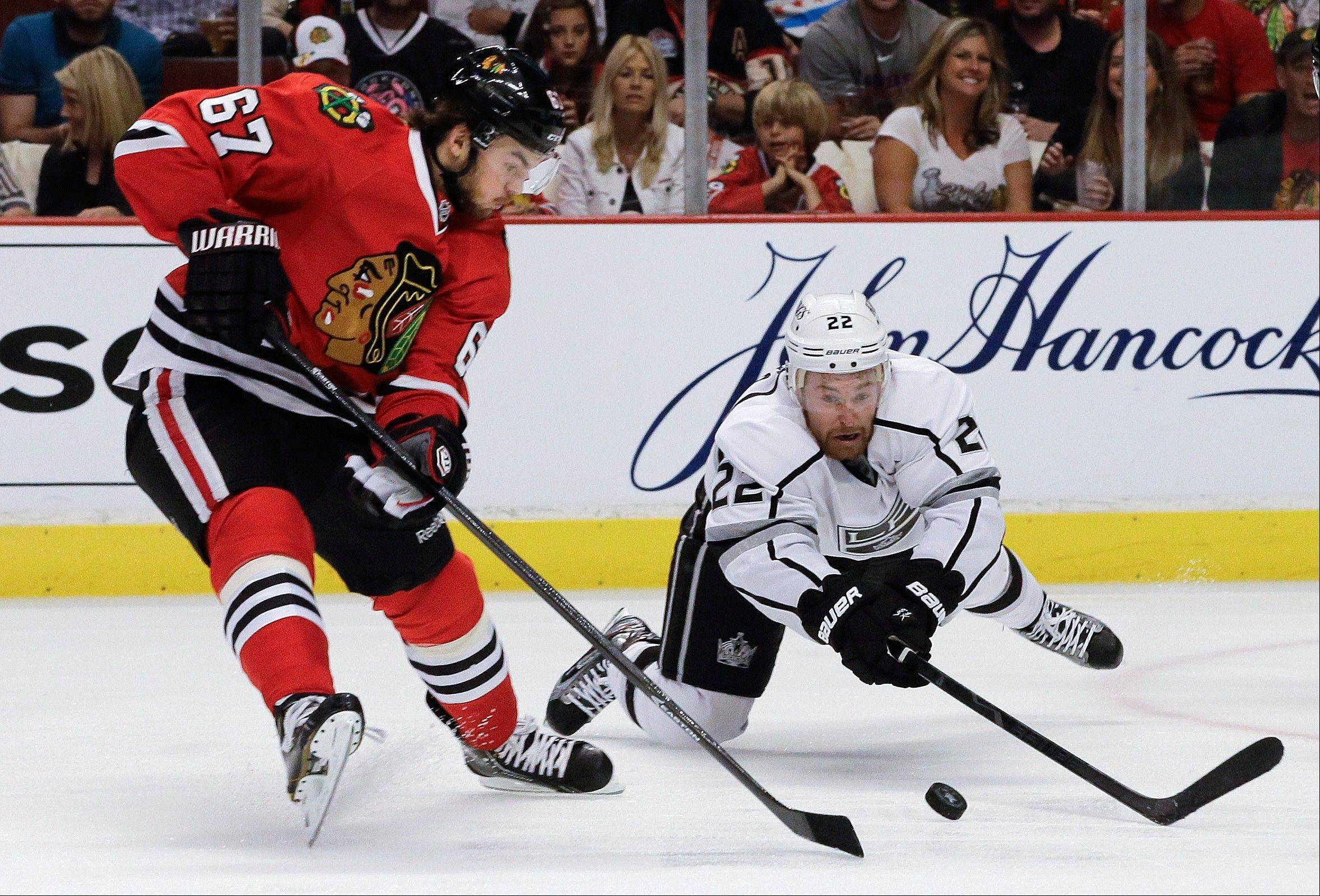 Los Angeles Kings center Trevor Lewis (22) dives for the puck against Chicago Blackhawks center Michael Frolik (67) during the second period of Game 1 of the NHL hockey Stanley Cup Western Conference finals, Saturday, June 1, in Chicago.