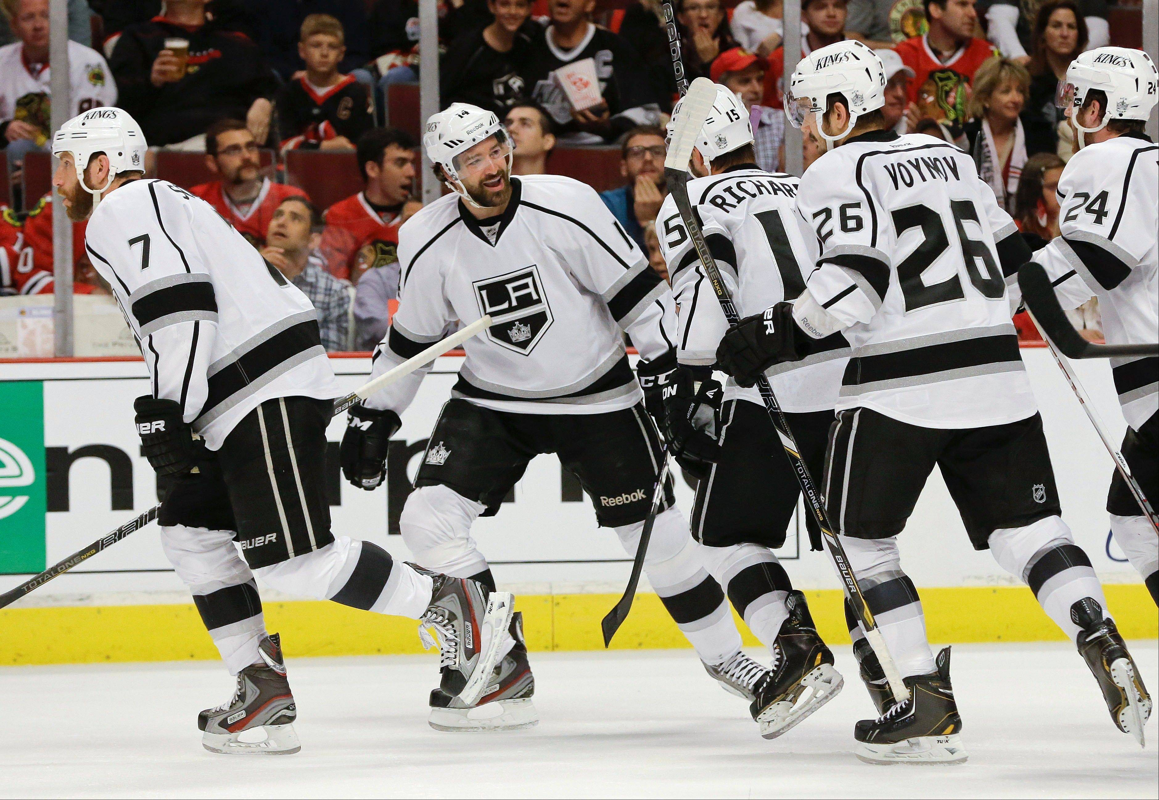 Los Angeles Kings right wing Justin Williams, second from left, smiles with teammates after scoring a goal against the Chicago Blackhawks in the first period of Game 1 of the NHL hockey Stanley Cup Western Conference finals, Saturday, June 1, 2013, in Chicago.