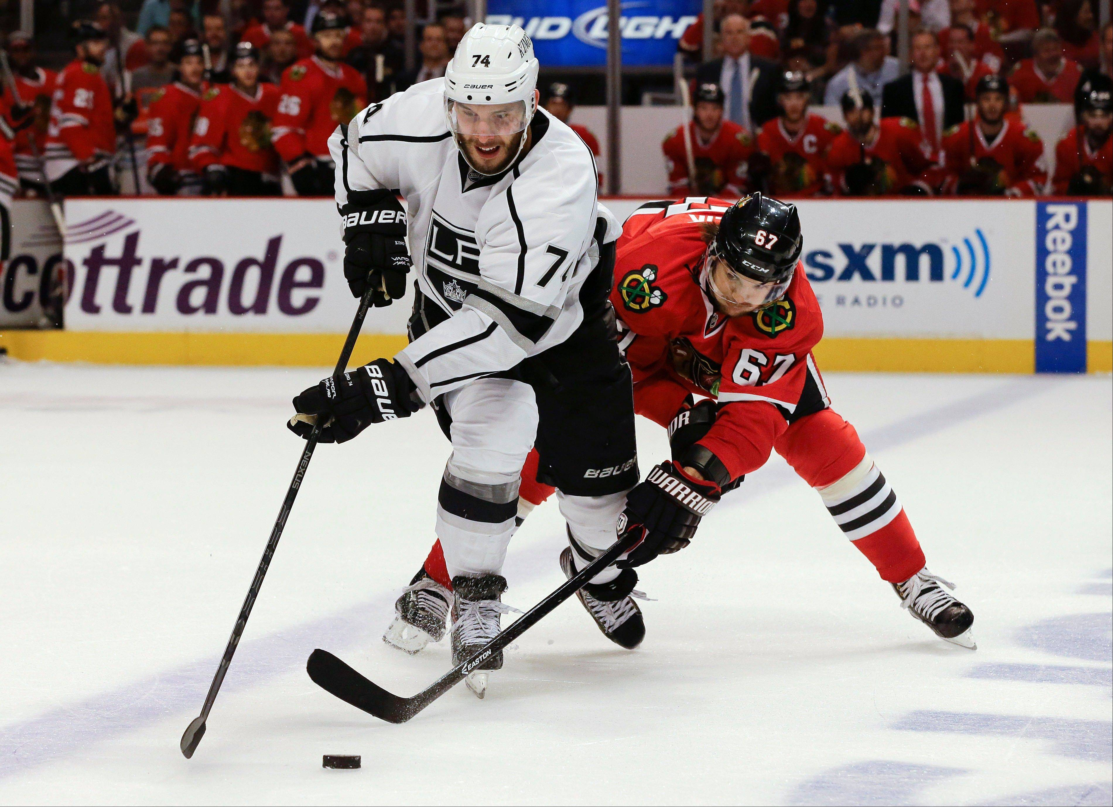 Los Angeles Kings center Dwight King (74) vies for the puck against Chicago Blackhawks center Michael Frolik (67) during the third period of Game 1 of the NHL hockey Stanley Cup Western Conference finals, Saturday, June 1, 2013, in Chicago. Chicago won 2-1.
