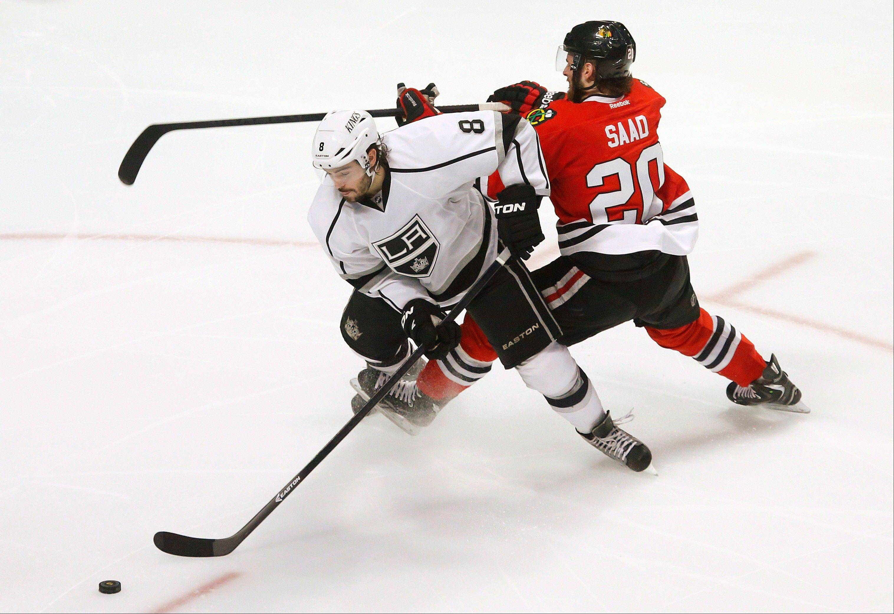 Los Angeles Kings defenseman Drew Doughty (8) gets tangled up with Chicago Blackhawks left wing Brandon Saad (20) during the third period in Game 1 of the NHL hockey Stanley Cup Western Conference finals Saturday, June 1, 2013, in Chicago.
