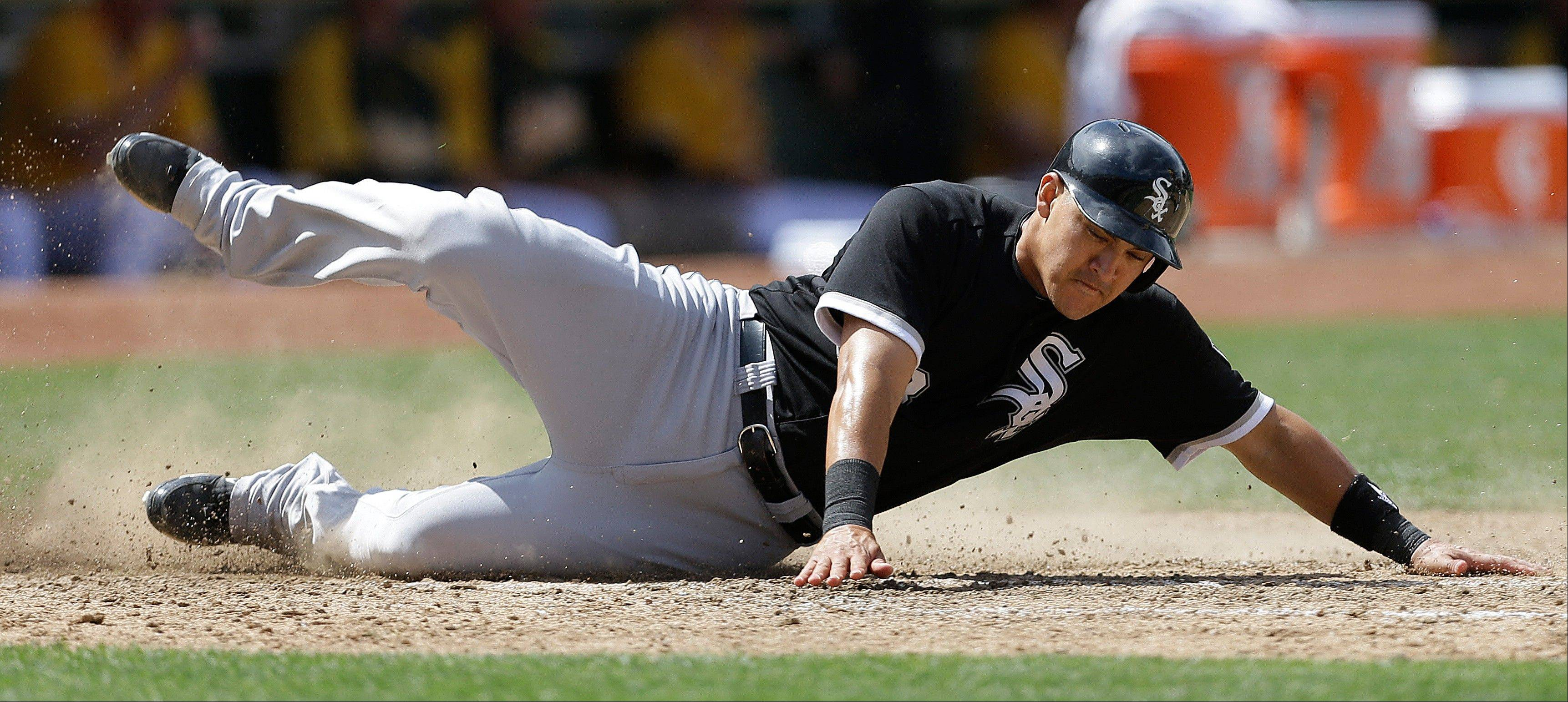 Chicago White Sox's Hector Gimenez slides into home plate to score against the Oakland Athletics in the seventh inning of a baseball game on Saturday, June 1, 2013, in Oakland, Calif. Gimenez scored on a single by Chicago's Alejandro De Aza.