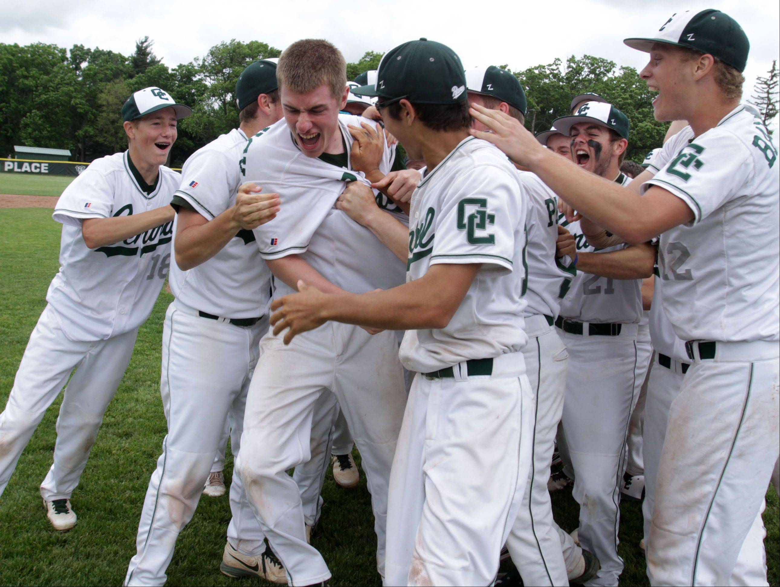 Grayslake Central relief pitcher Eric Skutnick, center left, is mobbed by teammates after recording the last out in the seventh inning as the Rams edged Wauconda 6-4 in Class 3A sectional final play Saturday.