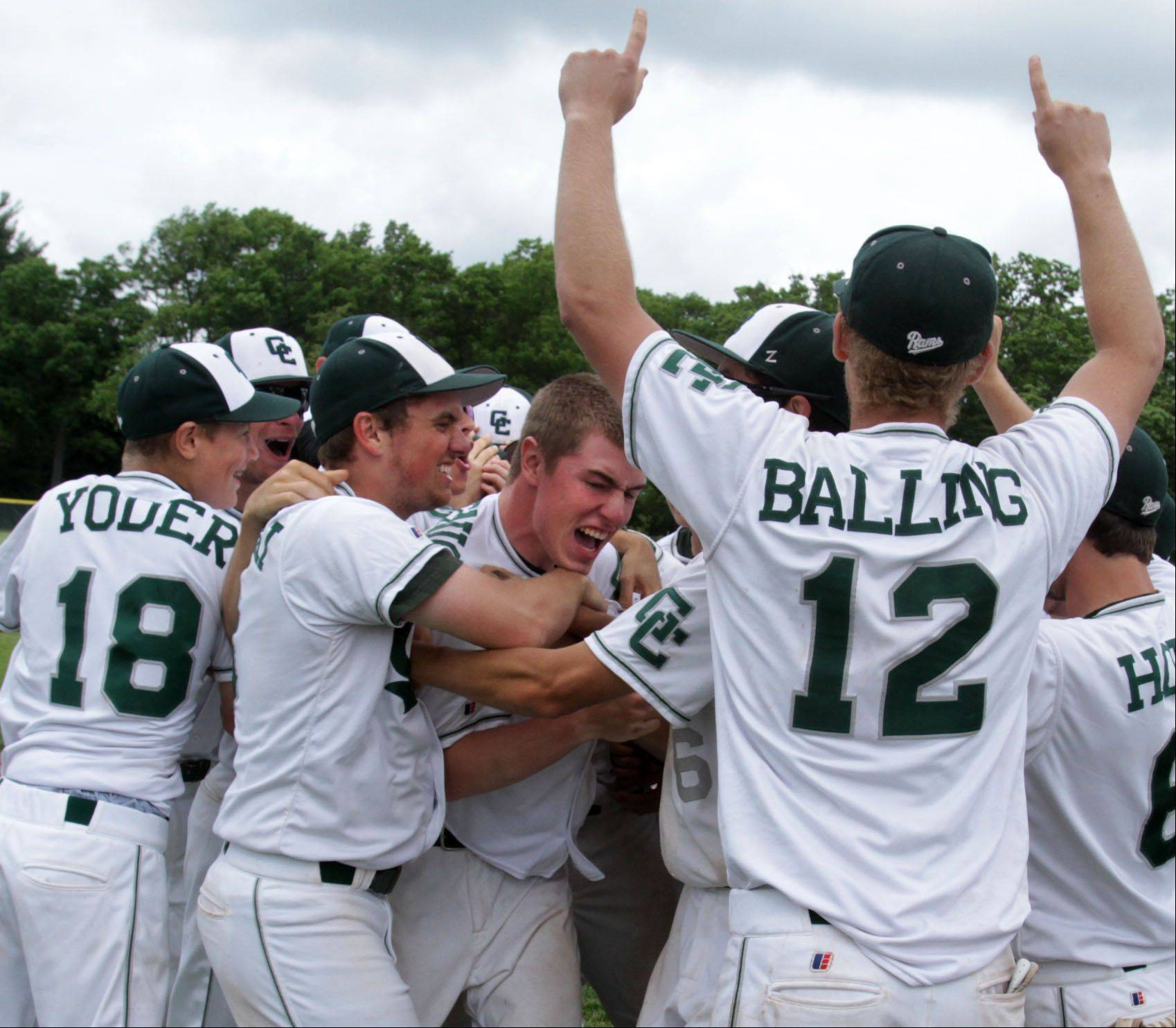 Grayslake Central reliever Eric Skutnick, center, is mobbed by teammates after recording the last out in the seventh inning as the Rams top Wauconda 6-4 in Class 3A sectional championship play Saturday.