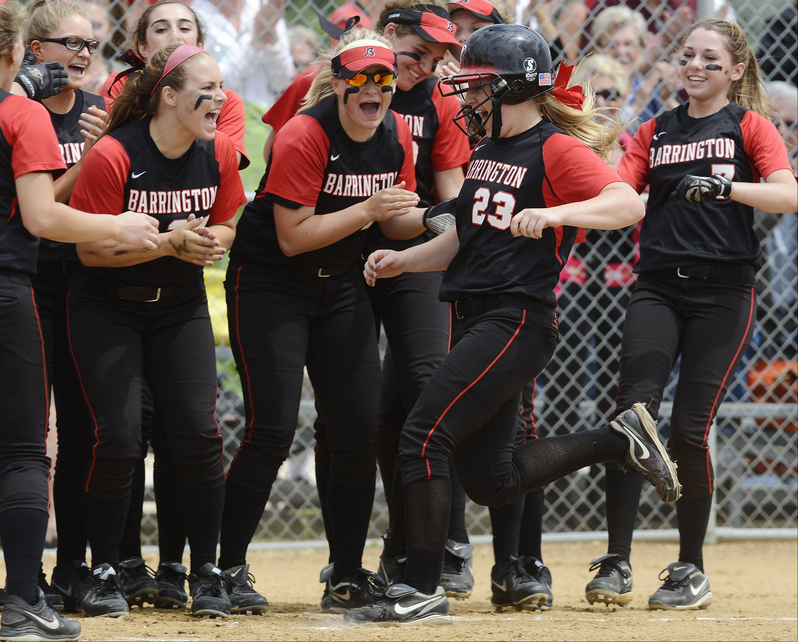 Barrington's Tess Bolger (23) is greeted at the plate by her teammates after hitting a leadoff home run against New Trier during the Rolling Meadows sectional final Saturday.