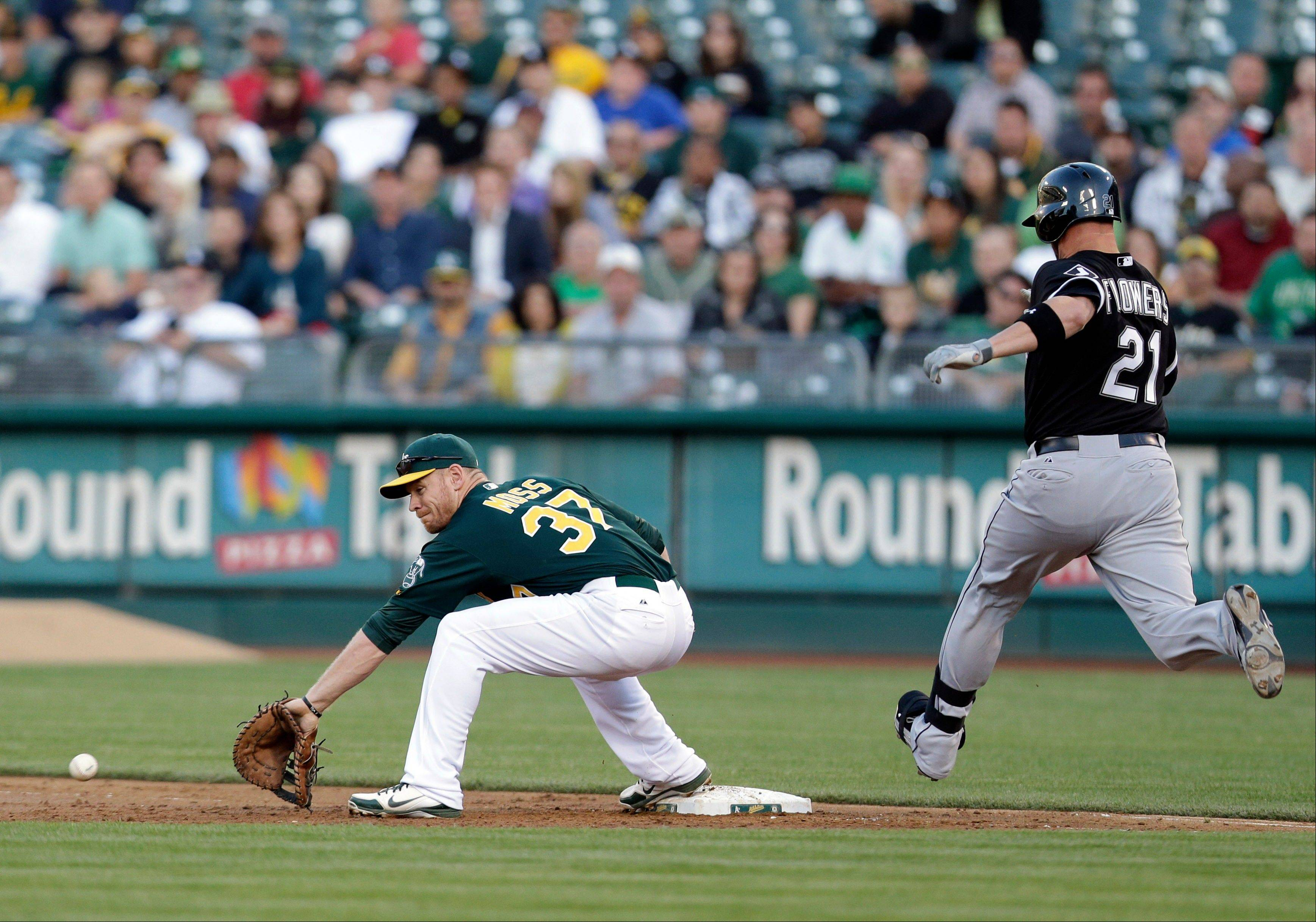 Oakland Athletics first baseman Brandon Moss, left, digs up a low throw from shortstop Jed Lowrie to put out Chicago White Sox's Tyler Flowers (21) during the third inning of a baseball game on Friday, May 31, 2013, in Oakland, Calif.