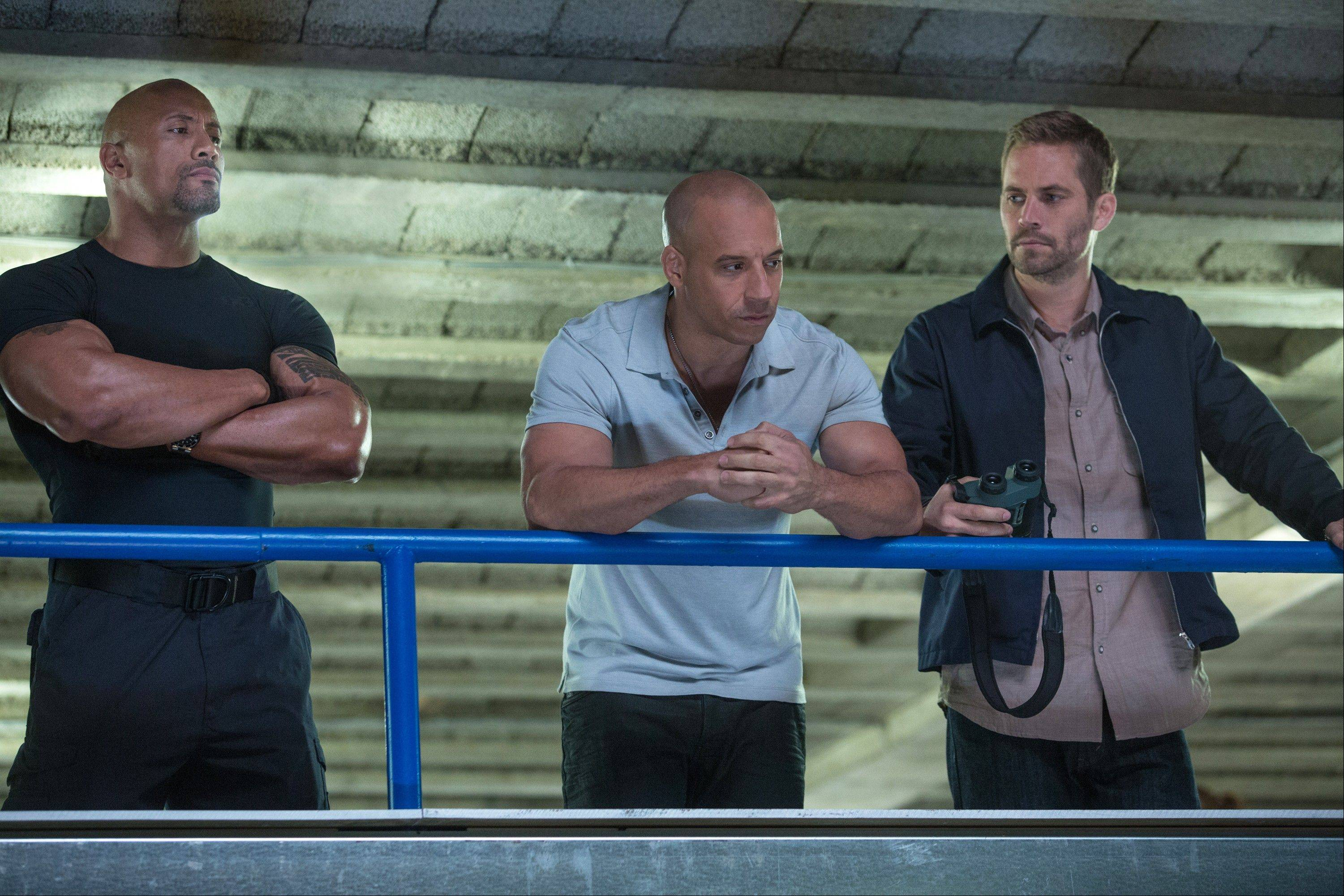 "Dwayne Johnson, left, Vin Diesel and Paul Walker star in ""Fast & Furious 6."" The sixth installment of the franchise kept its hold on the box office with a $34.5 million haul."