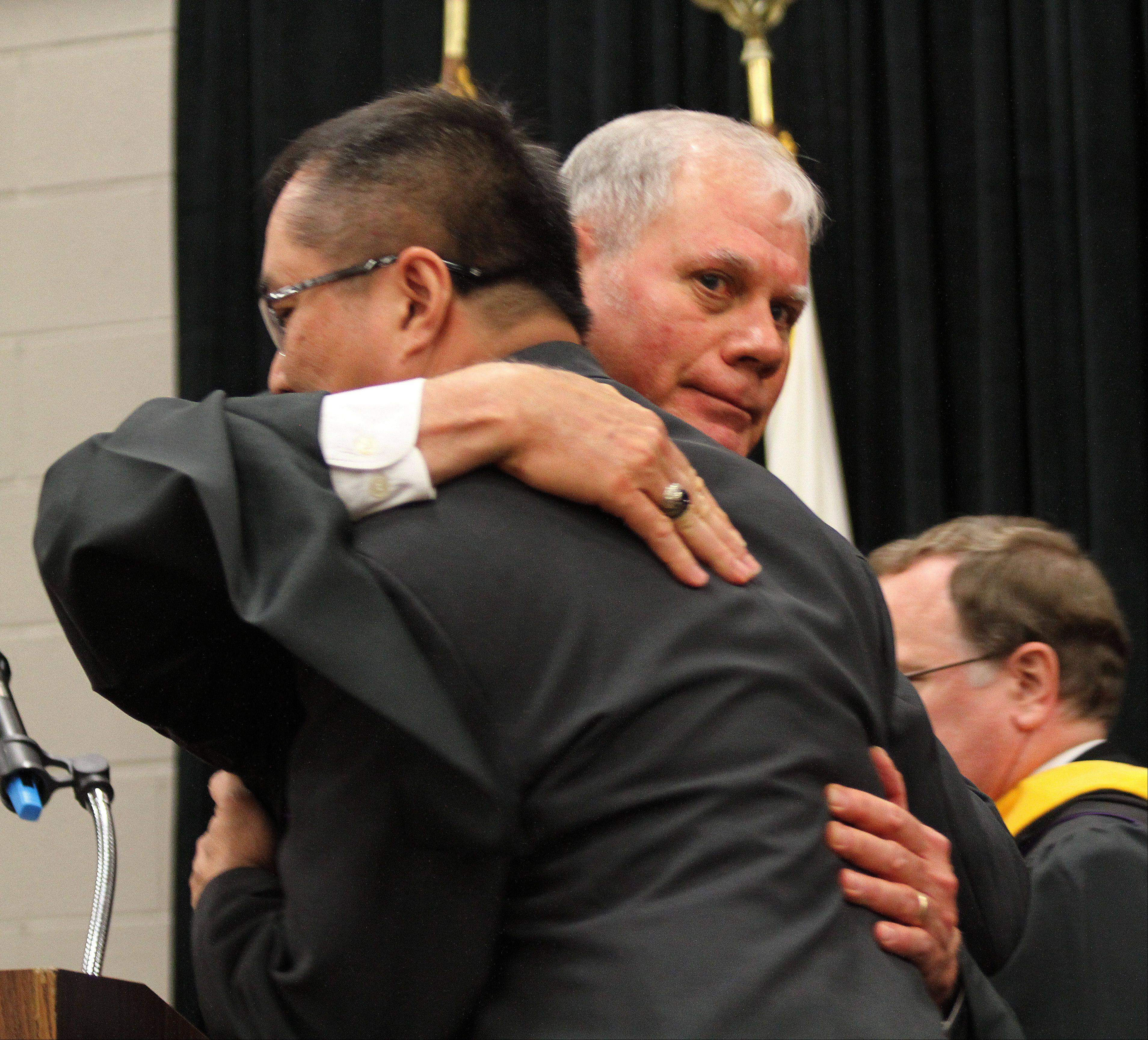 James Brown, right, the assistant principal of Benet Academy, hugs the father of Jennie Dizon, left, after presenting her family with her diploma to mark her graduation on Sunday, June 2.