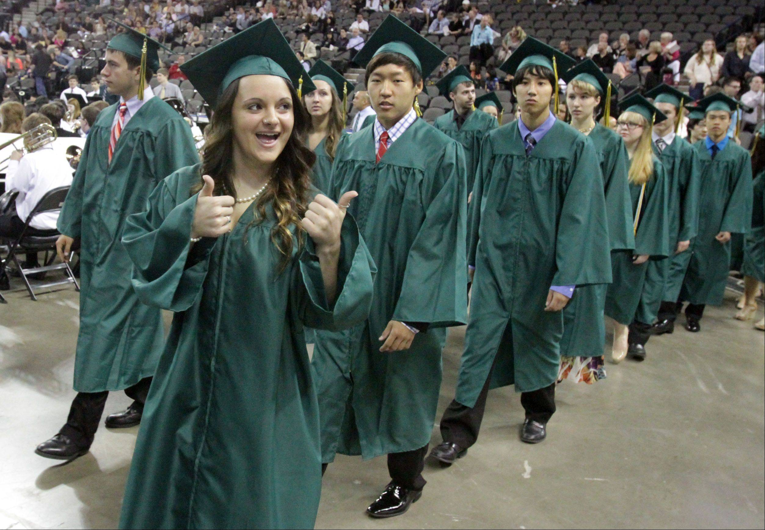 Christina Nowicki gives the thumbs-up to her family as she marches with graduates into the Sears Centre for Fremd High School's commencement ceremony on Sunday.